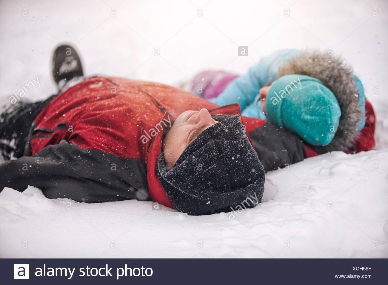 Vater und Tochter tragen stricken Mützen liegen auf dem Rücken im Schnee Stockbild