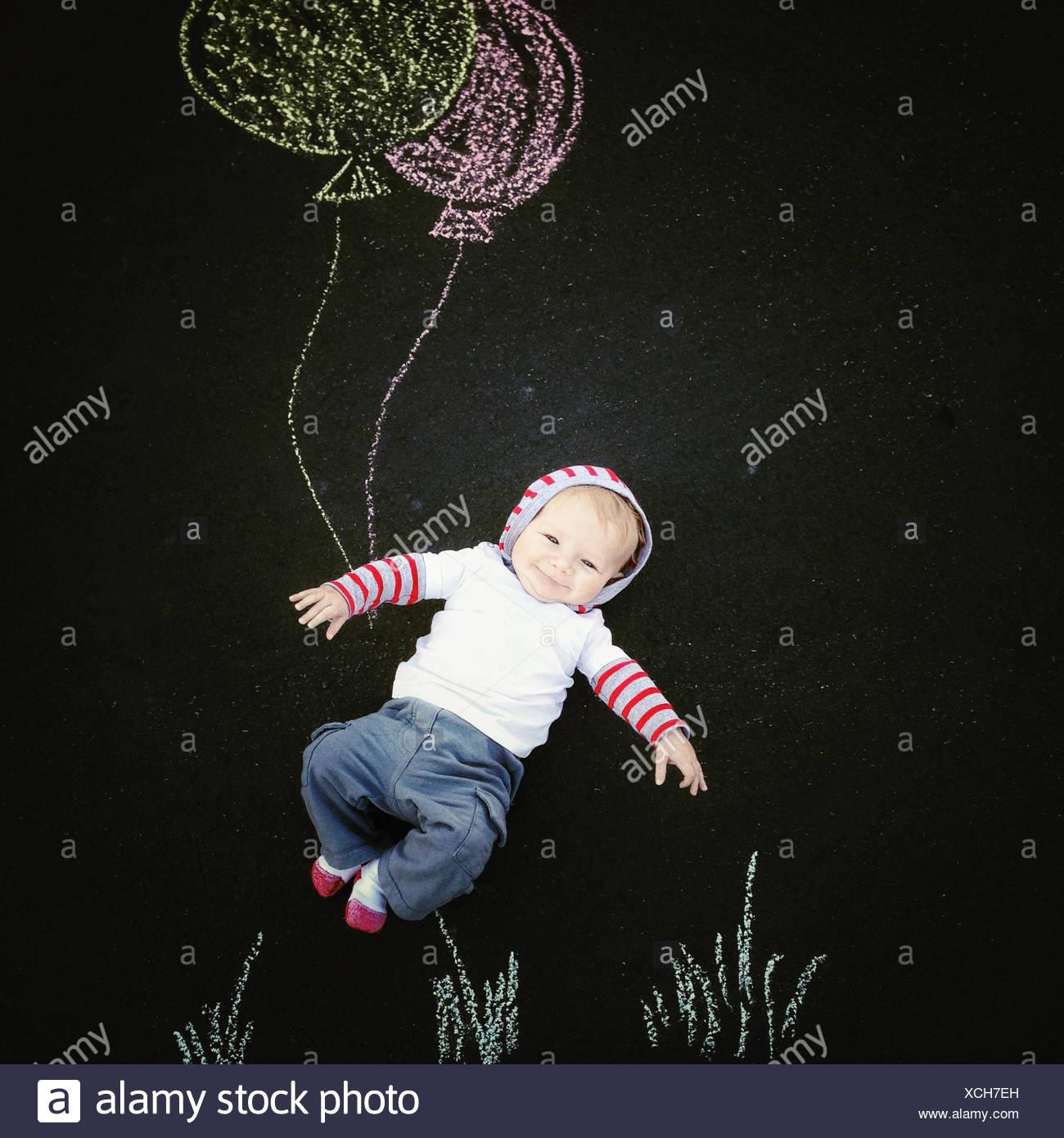 Baby Boy mit Kreidezeichnung von Luftballons Stockbild