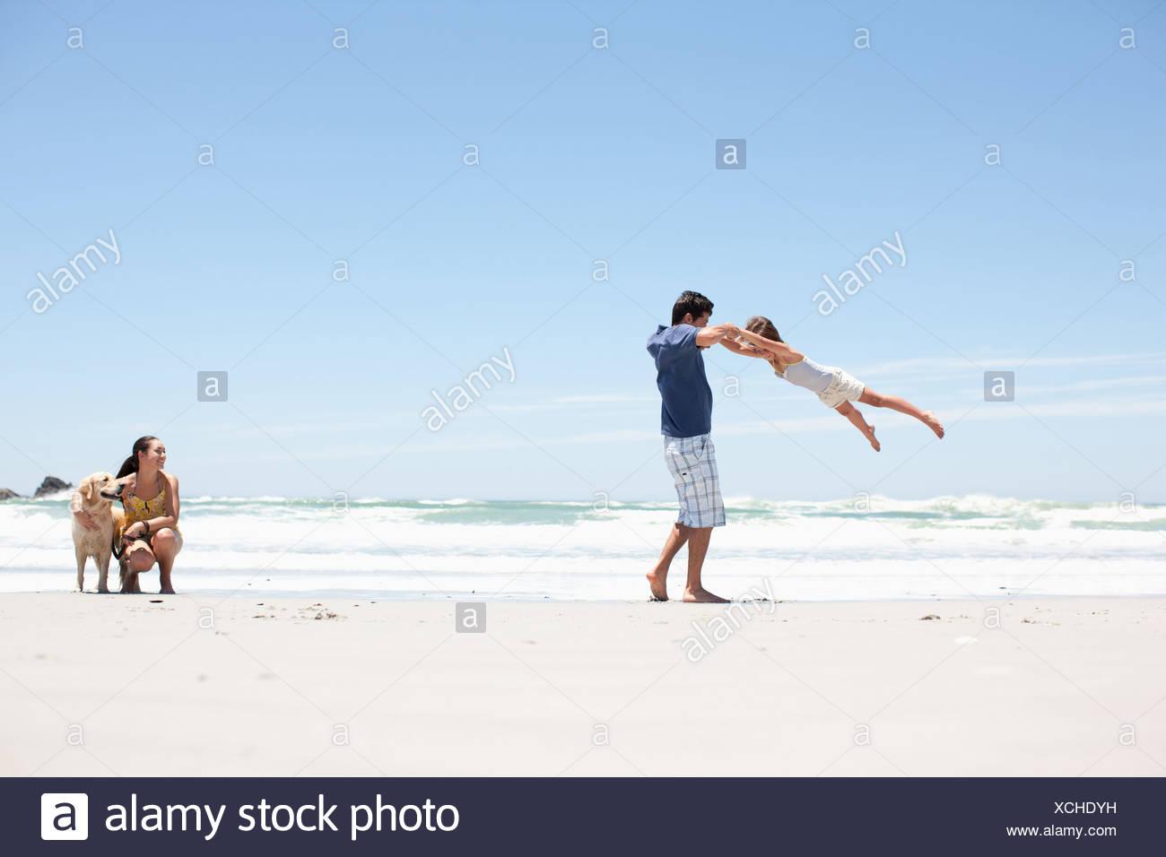 Familie mit Hund am Strand spazieren Stockbild