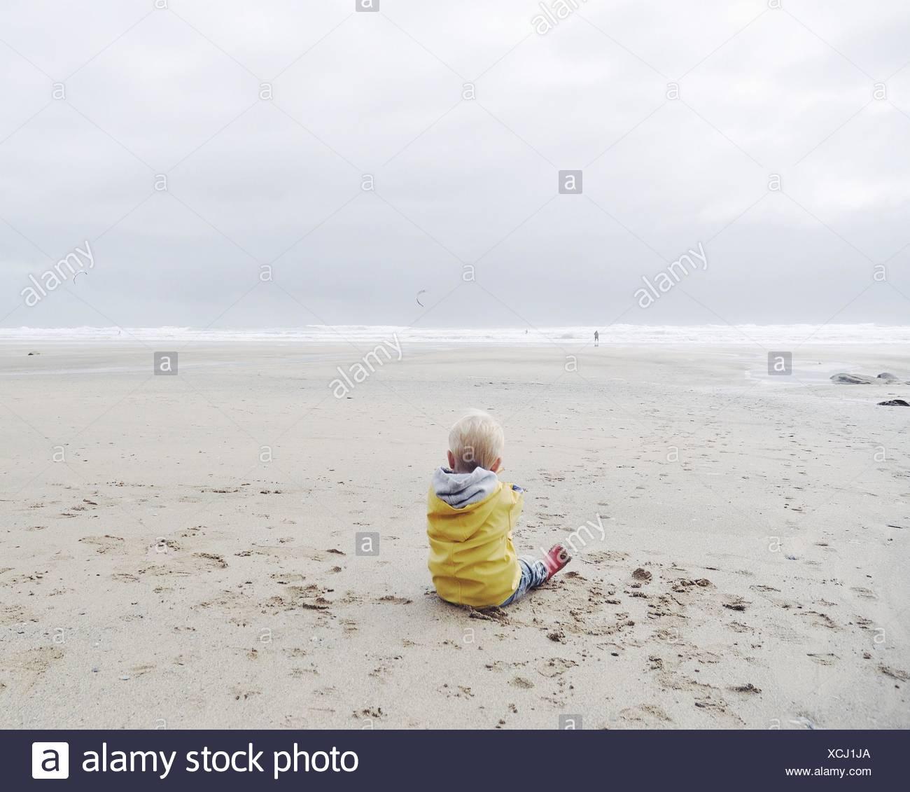 Rückansicht der Junge sitzt am Strand in einem Regenmantel Stockbild