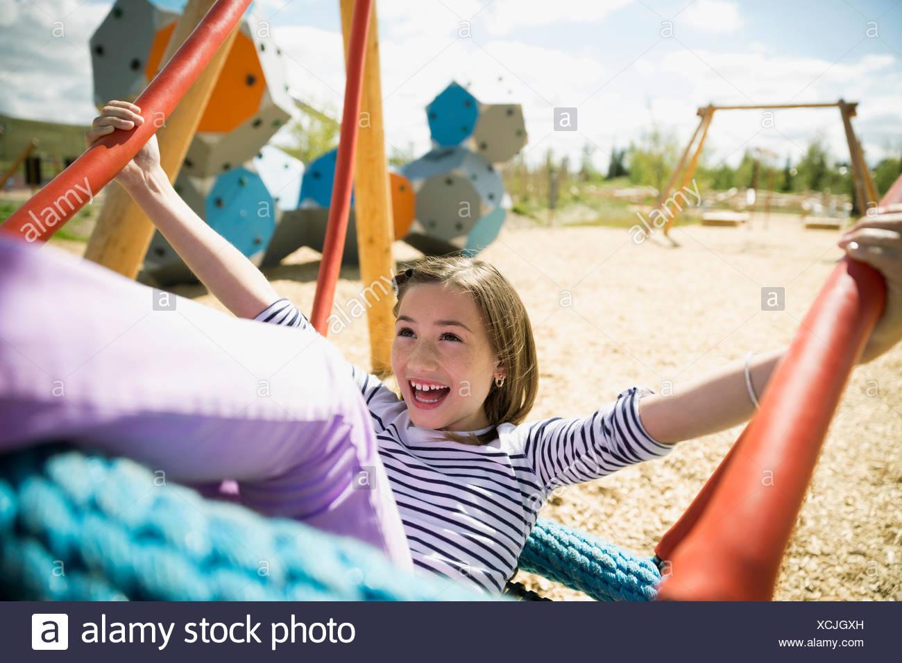 Begeisterte Mädchen schwingen auf sonnigen Spielplatz Stockbild