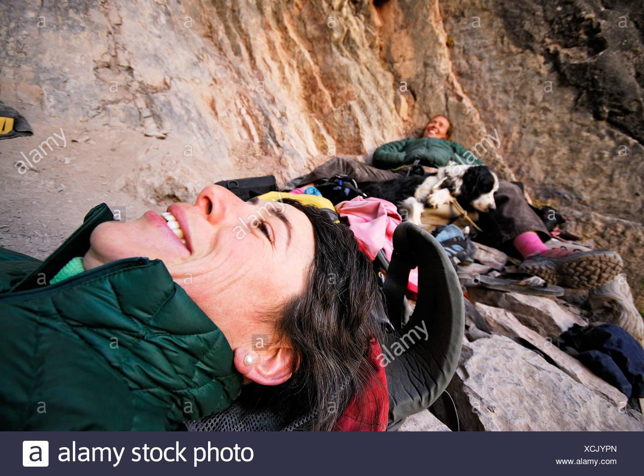 Zwei Kletterer hinlegen und entspannen Sie sich am Fuße der steilen Wand. Stockbild