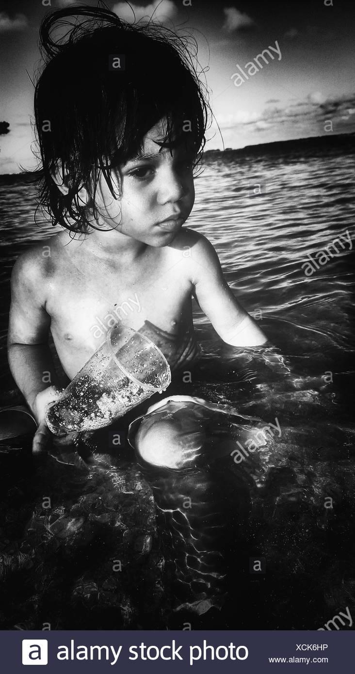 Süsser Boy mit Glasbehälter sitzen im Meer Stockbild