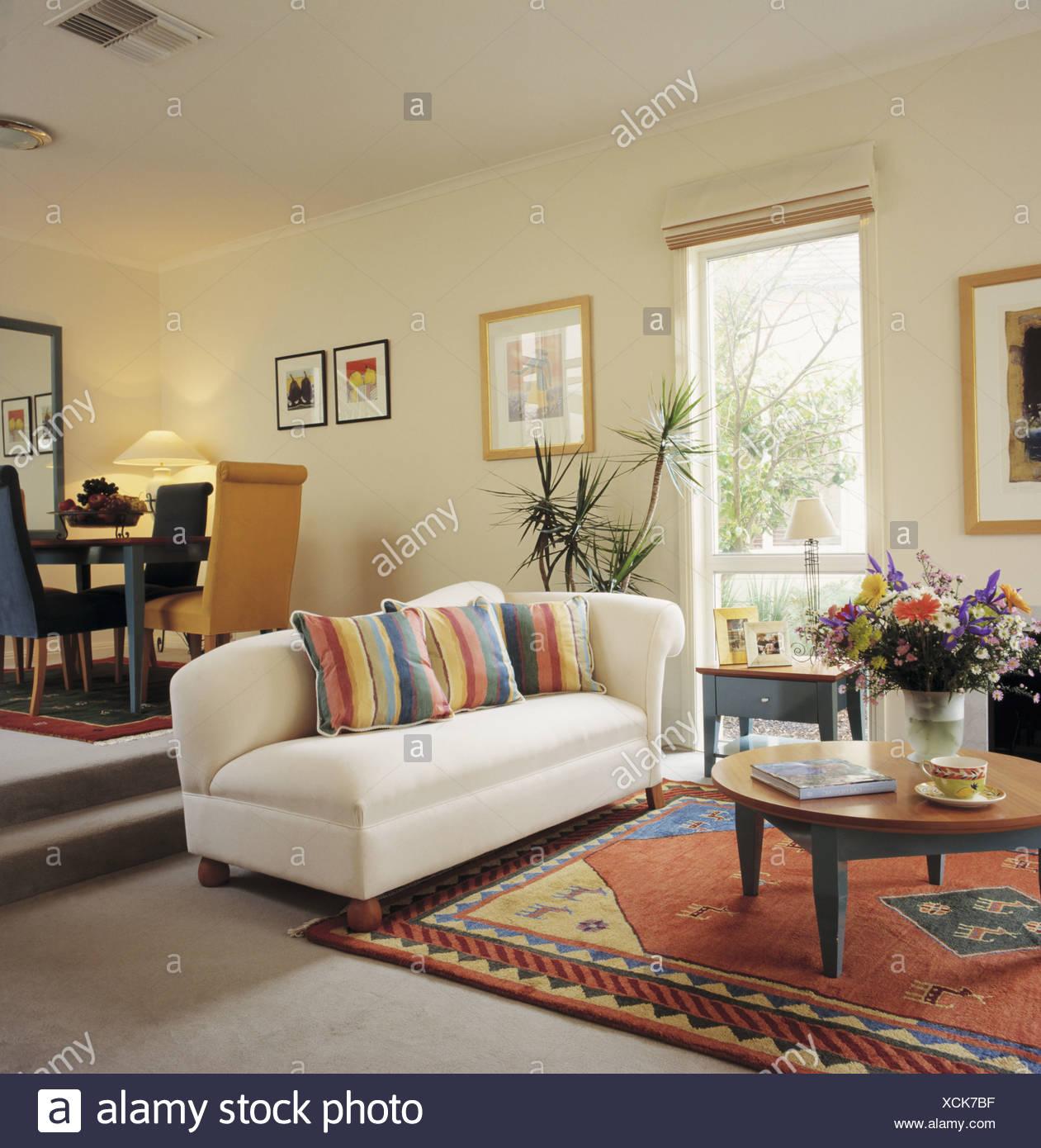 Bunt gestreifte Kissen auf weißen Sofa und gemusterten Teppich in ...