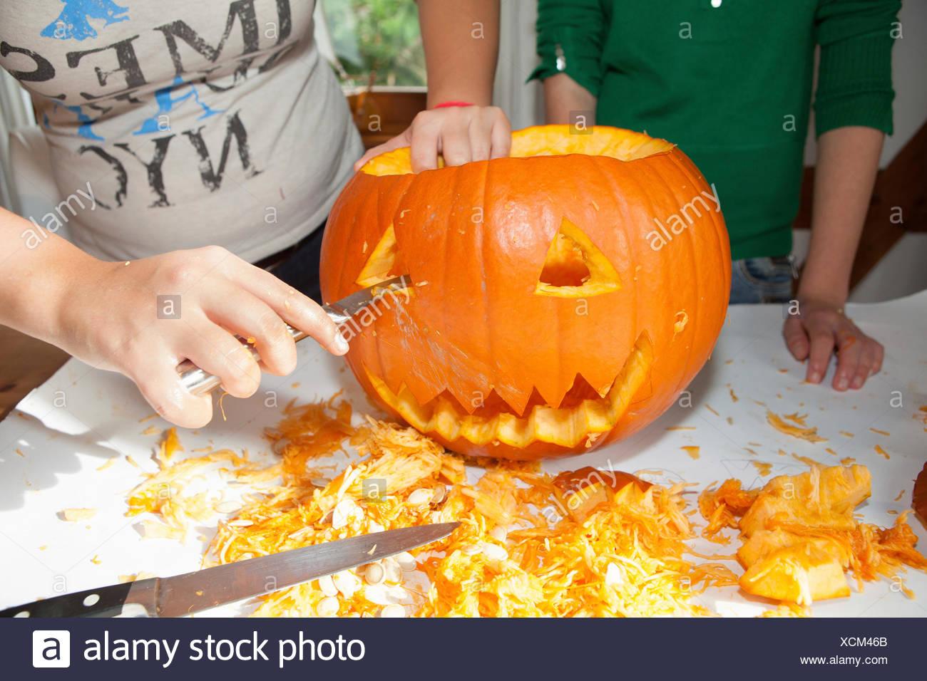 Zwei Mädchen, etwa 14 Jahre ein Gesicht in einen Halloweenkürbis schnitzen Stockfoto