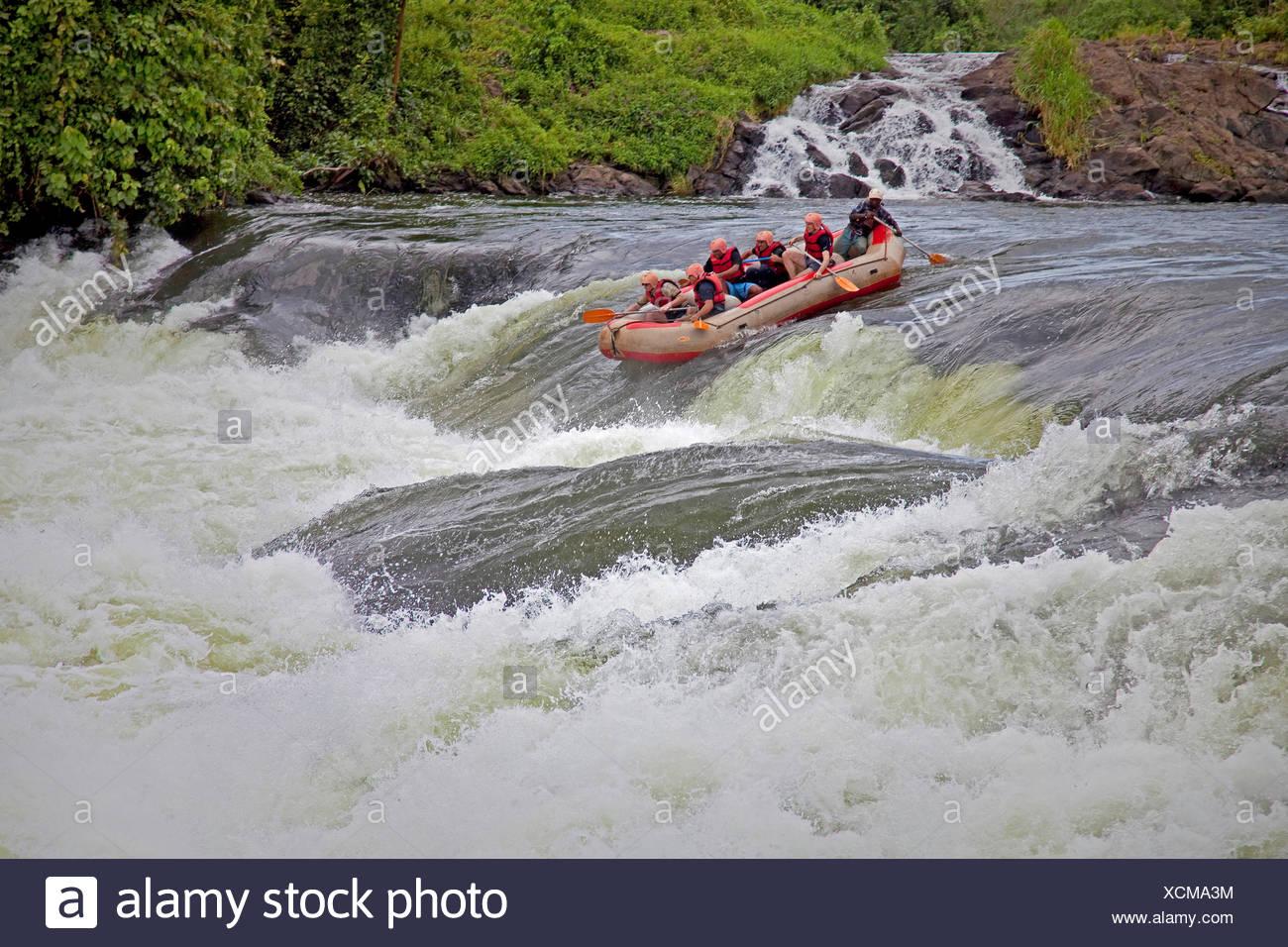 Touristen mit einem lokalen Führer sind rafting auf die Bujagali Wasserfälle und sind im Begriff, eine wilde schnelle, Uganda, Jinja erreichen Stockbild