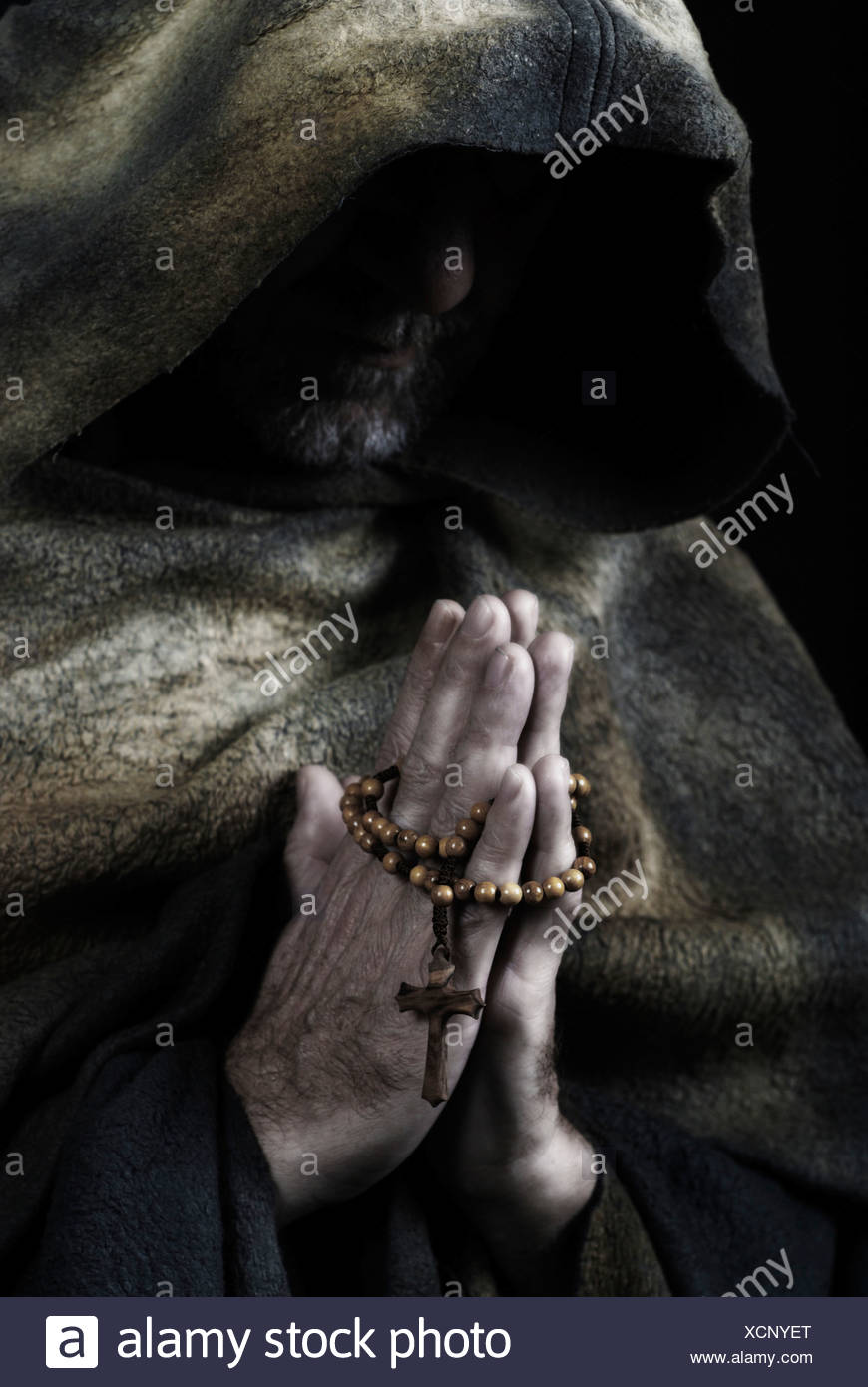 Mönch in Gewohnheit halten Rosenkranz beten Stockbild