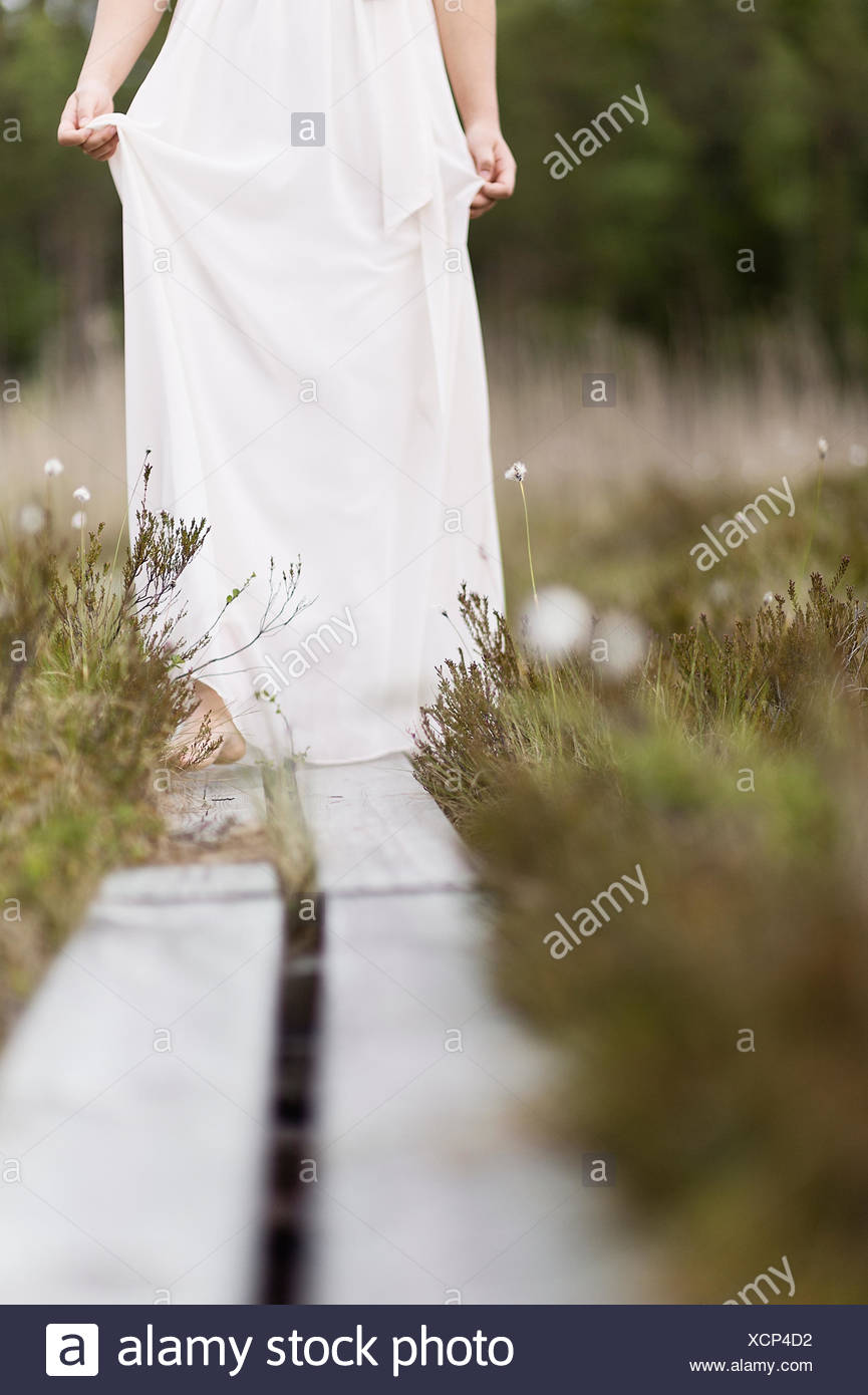 Schweden, Vastmanland, Teenage Girl (16-17) im weißen Kleid stehend auf Überführung in Wiese Stockbild