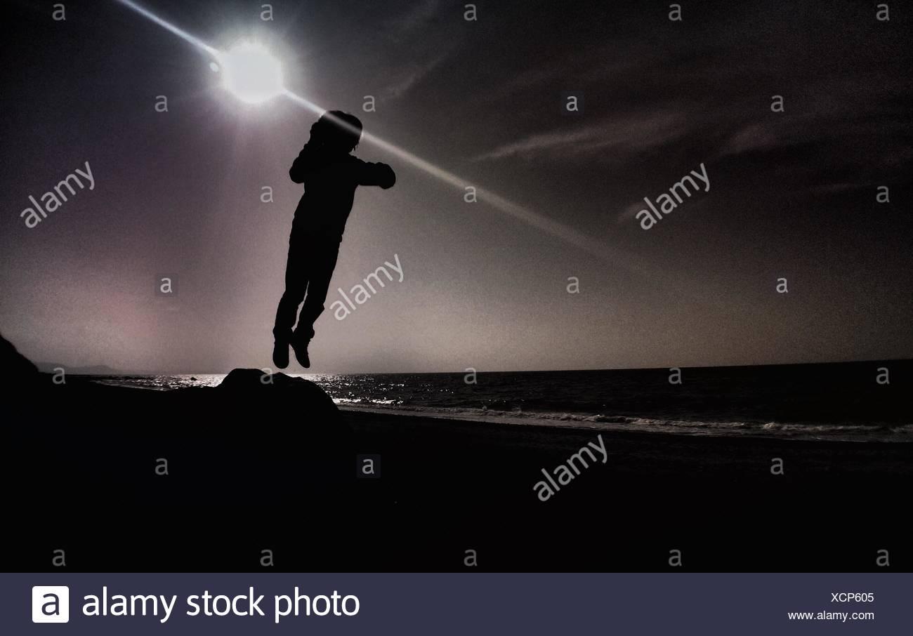 Person springt in die Luft gegen Sonne Stockbild