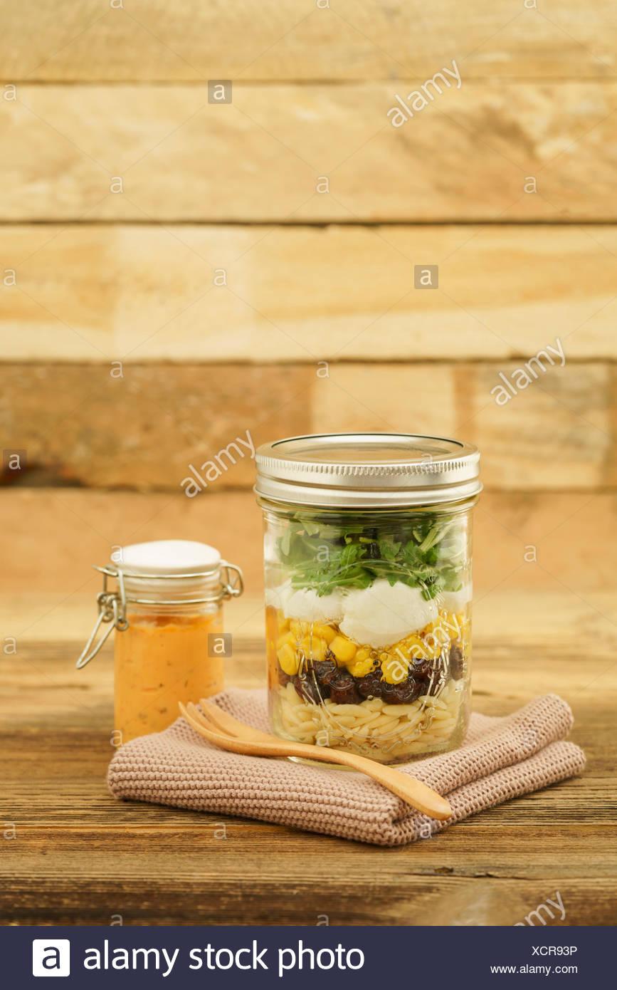 Vegetarischer Salat zum Mitnehmen im Glas mit Kritharaki, Cranberries, Mais, Mozzarella, Rucola und Cocktail-Dressing Stockbild