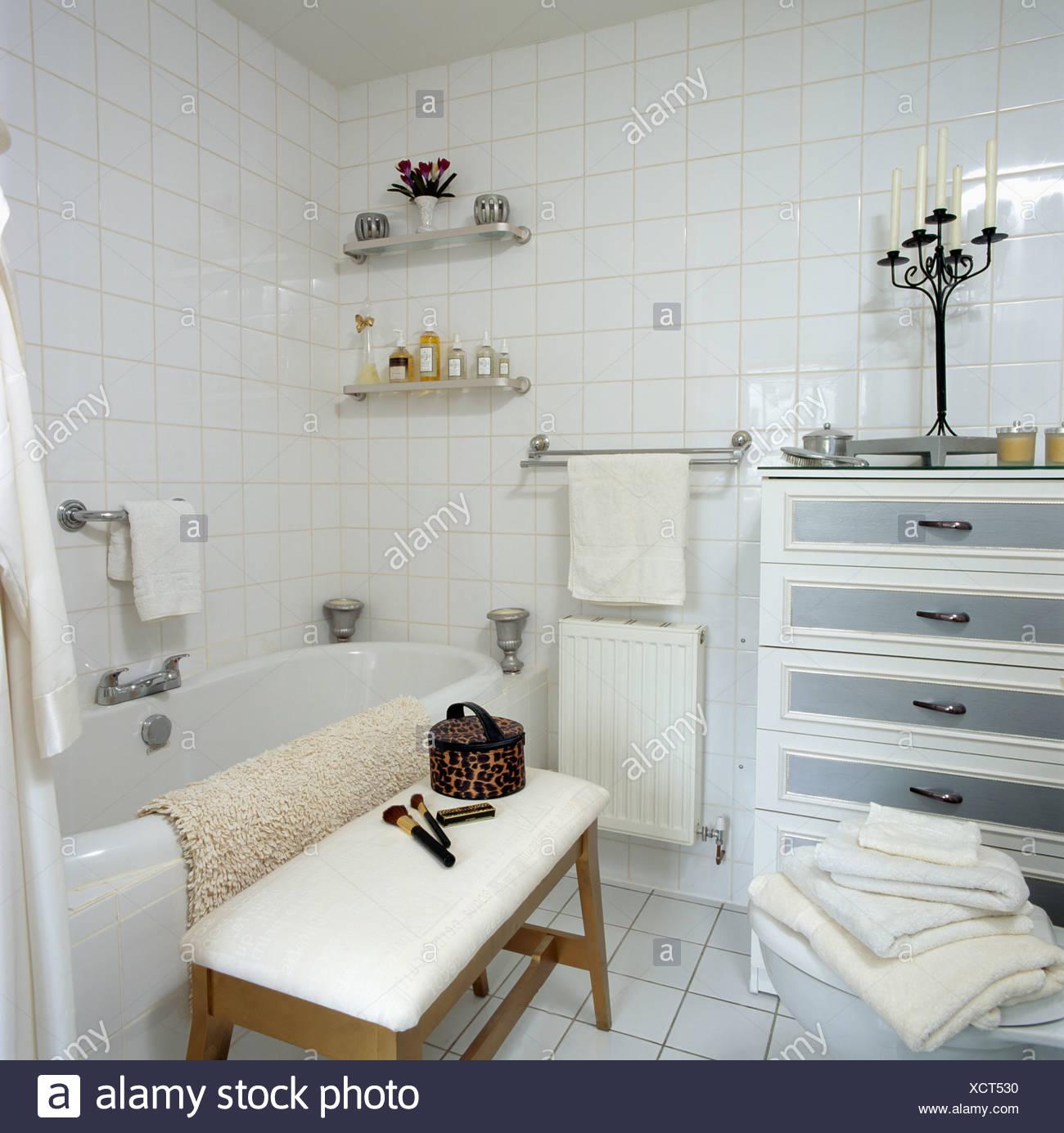 Weiß geflieste Badezimmer mit kleinen Kommode und gepolsterten ...