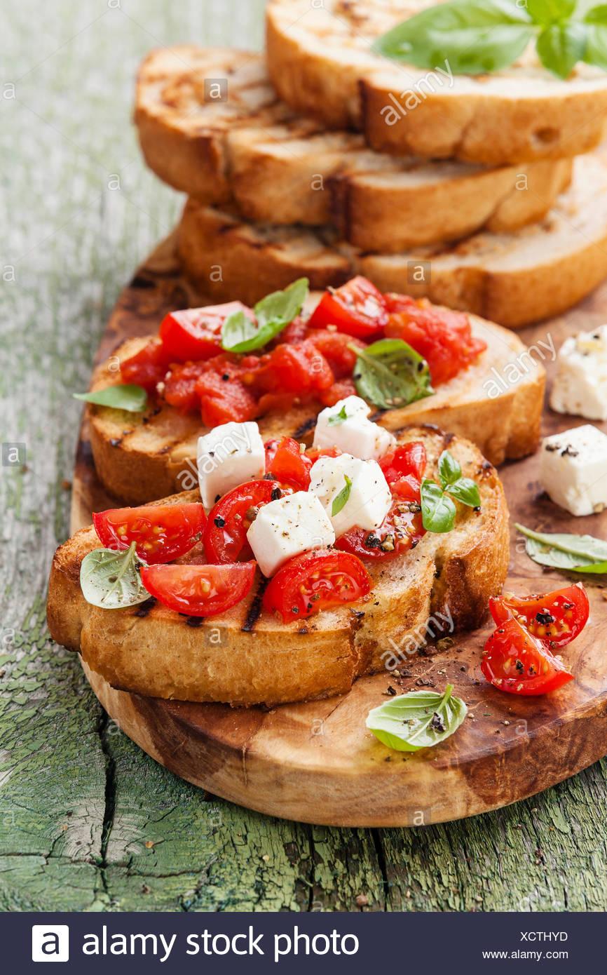 italienische bruschetta mit tomaten basilikum und k se auf gegrilltem knusprigem brot stockfoto. Black Bedroom Furniture Sets. Home Design Ideas
