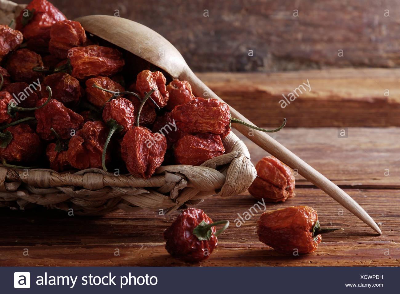 Mini-Paprika (Paprika) in einem Weidenkorb auf einem rustikalen hölzernen Hintergrund Stockbild