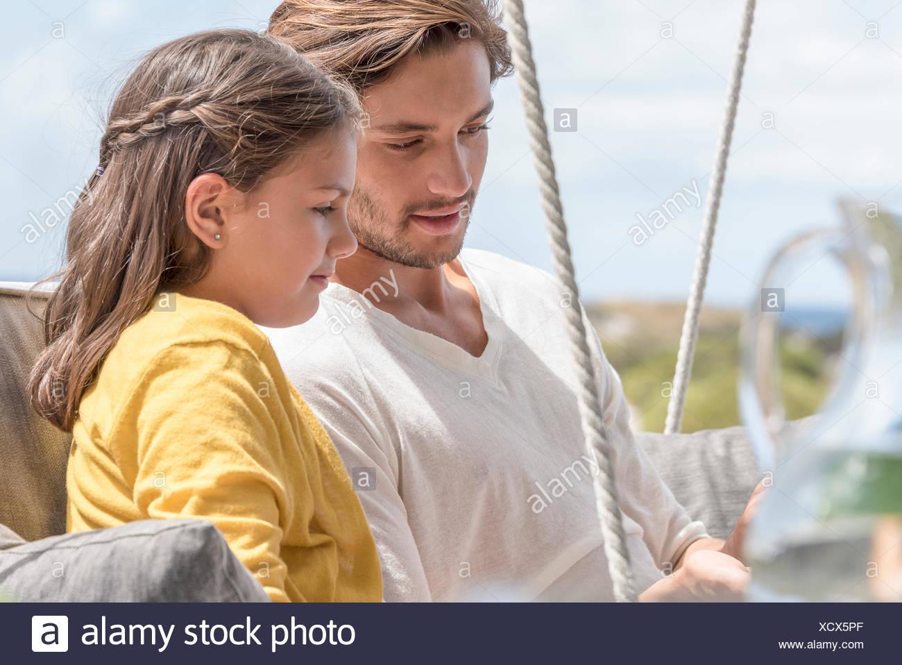 Glücklicher Vater mit seiner kleinen Tochter zusammen auf Schaukel Stuhl sitzend Stockbild
