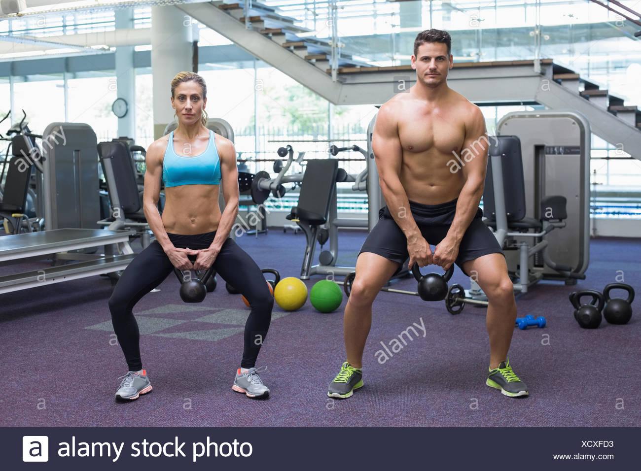 Bodybuilding-Mann und Frau heben Kettlebells in einem besetzten Haus Stockbild