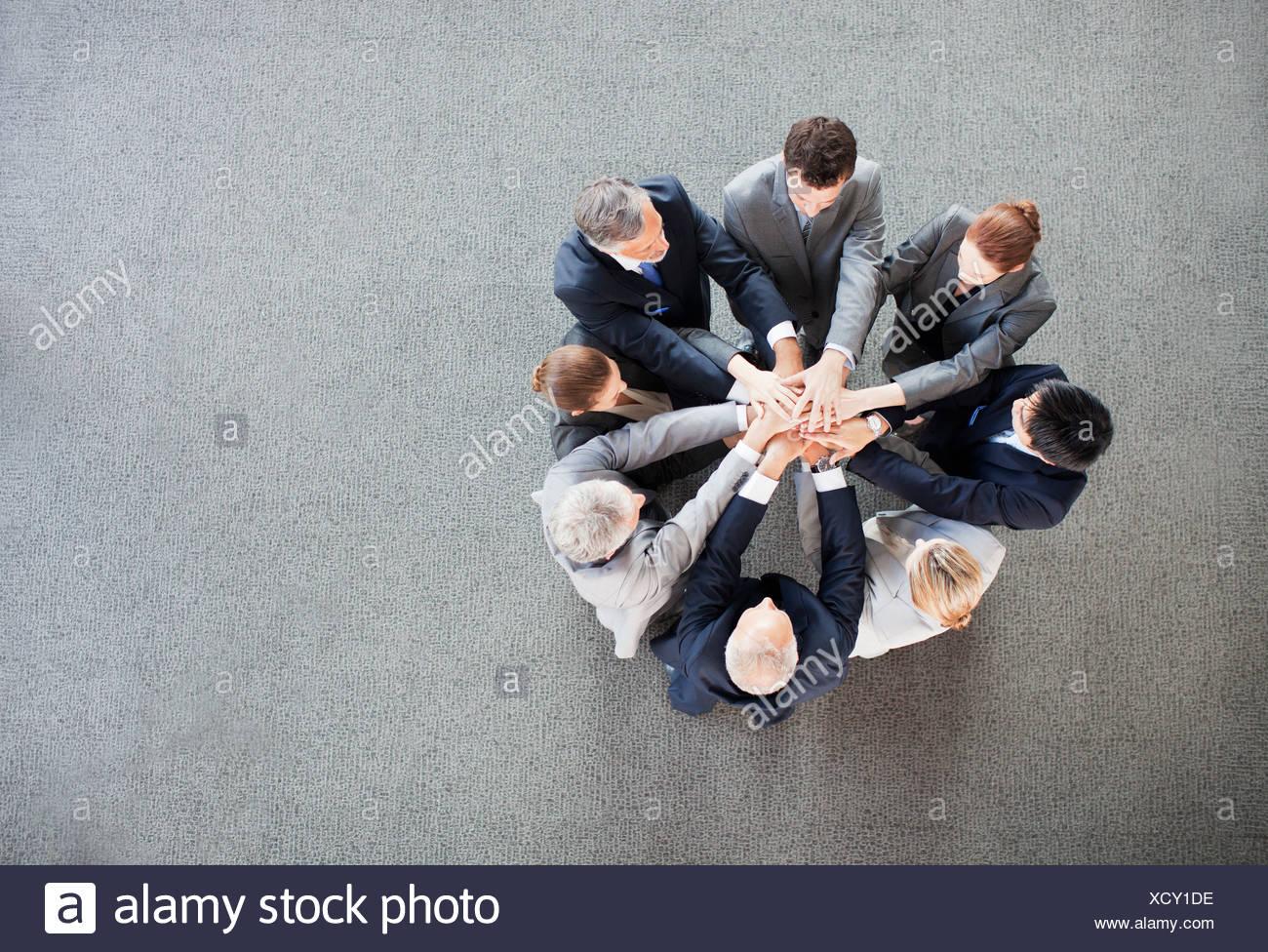 Geschäftsleute, die Hände im Kreis stapeln Stockbild
