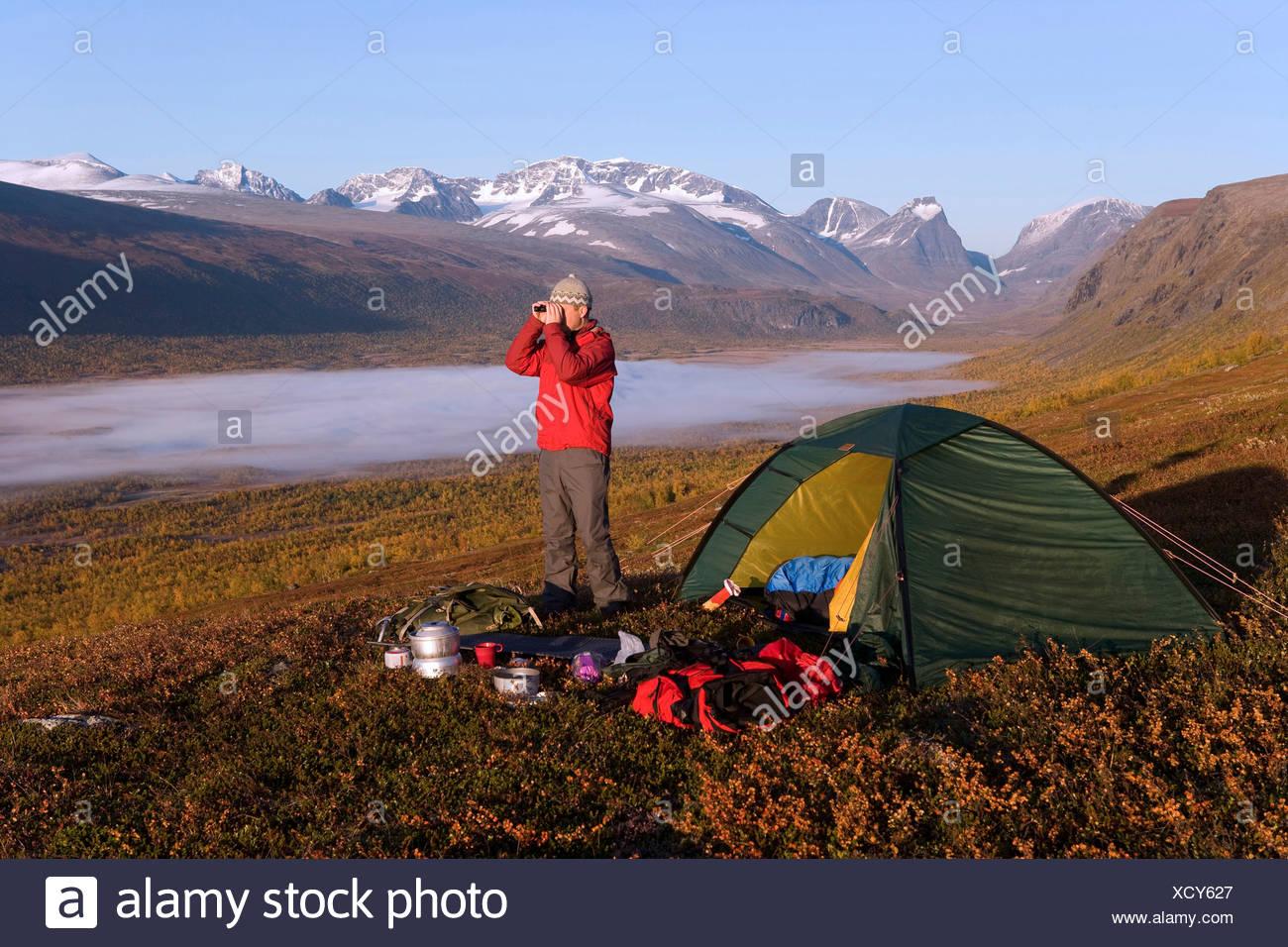 Wanderer mit dem fernglas von zelt und nebel auf landschaft mit