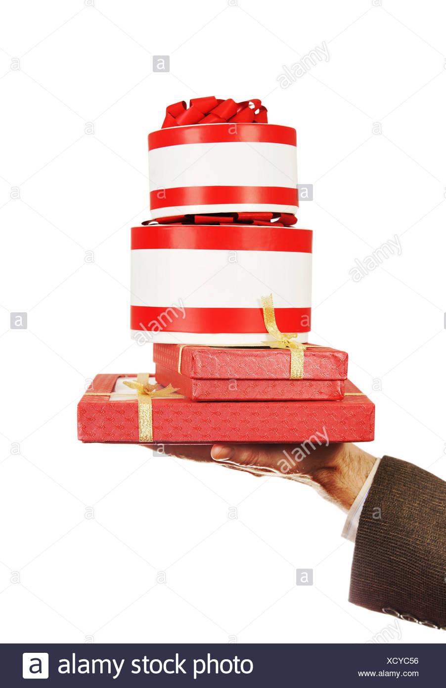 Viele Geschenke auf eine männliche Hand isoliert auf weiß Stockbild