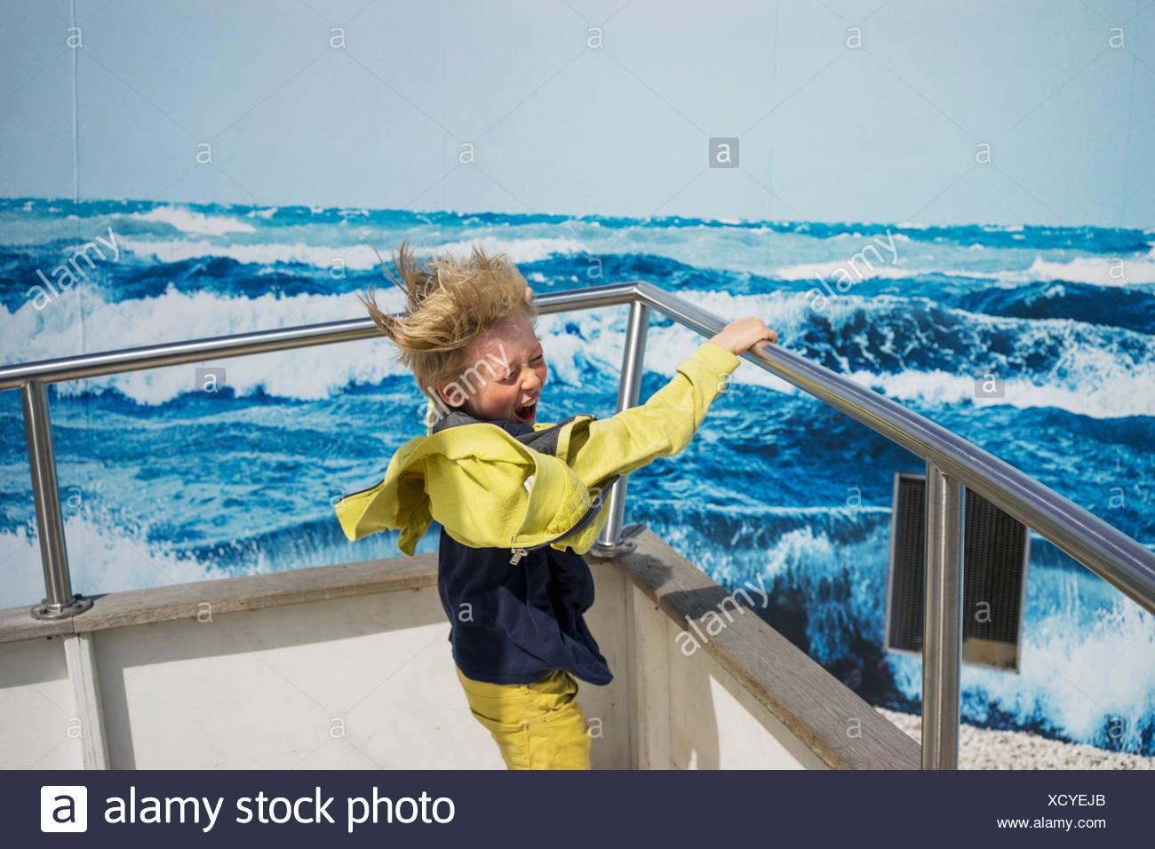 Ein Junge auf einem Boot bei nassem Wetter Gang Stockbild