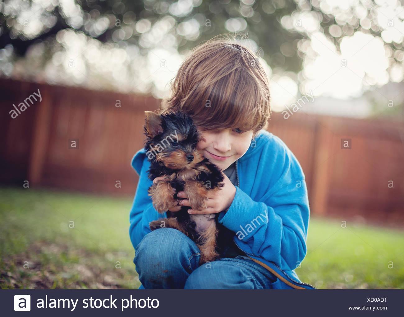 Junge seine Yorkie Welpen Hund kuscheln Stockfoto