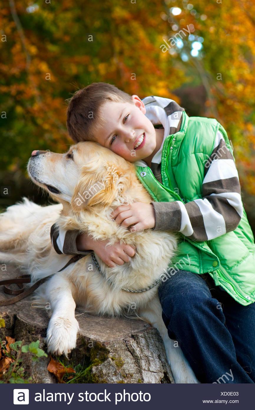 Porträt des jungen umarmt Hund auf Baumstumpf Stockbild