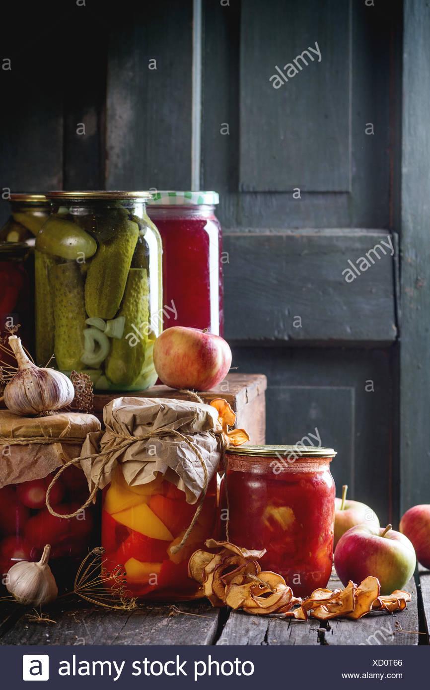 Sammlungssatz für viele hausgemachte Gläsern mit Essen (Gurken, Tomaten, Paprika), mit Knoblauch und frisch konserviert und getrocknet eine Stockbild