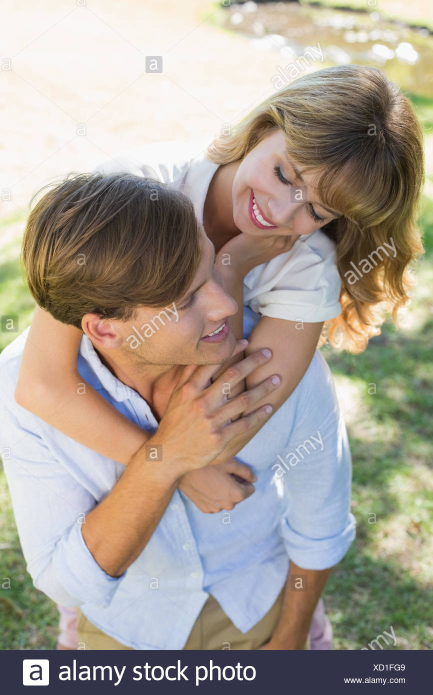 Mann mit seiner hübschen Freundin Huckepack im Park Lächeln einander an Stockbild