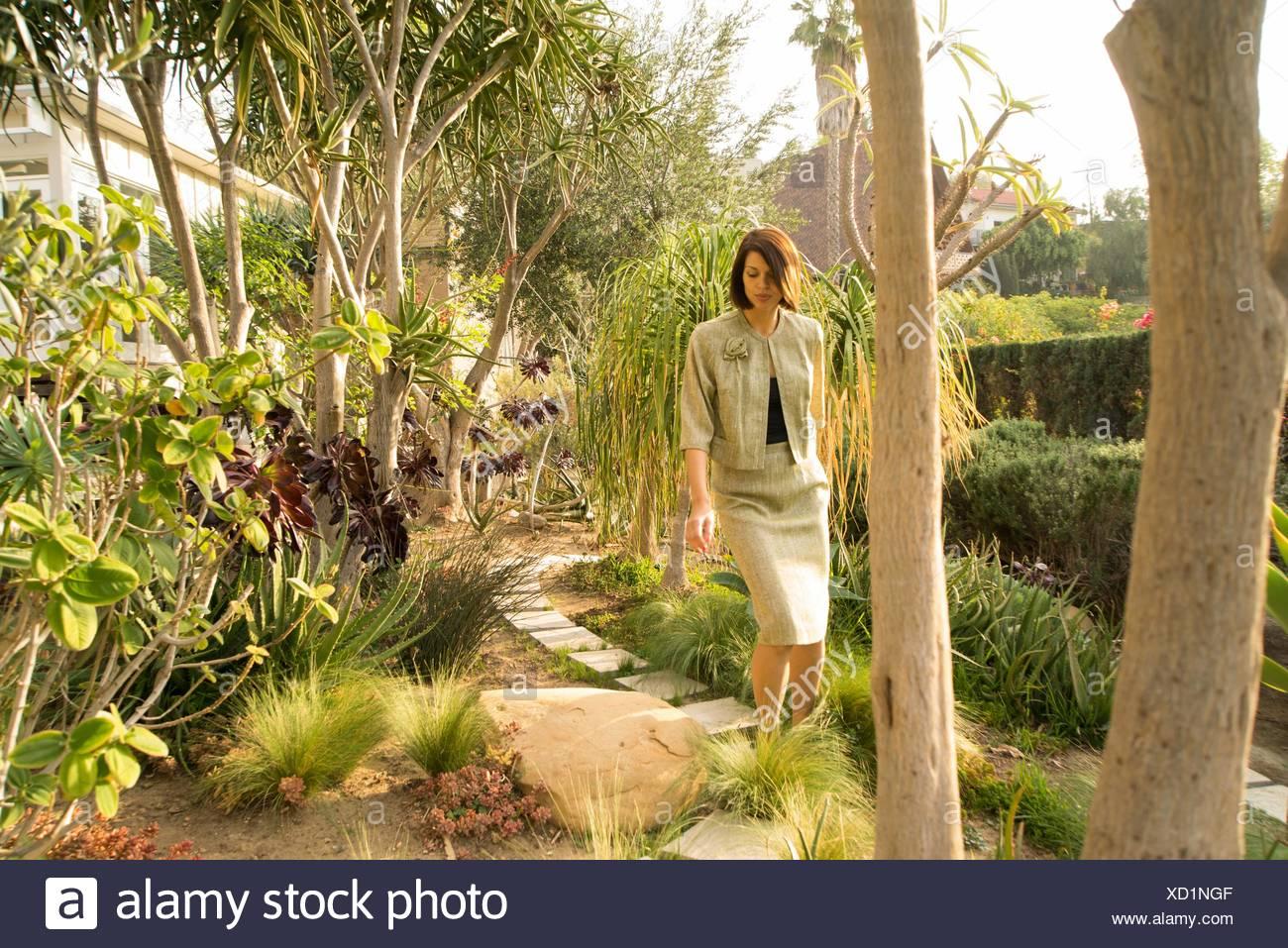 Anspruchsvolle Mitte Erwachsene Frau einen Spaziergang im Garten Stockbild