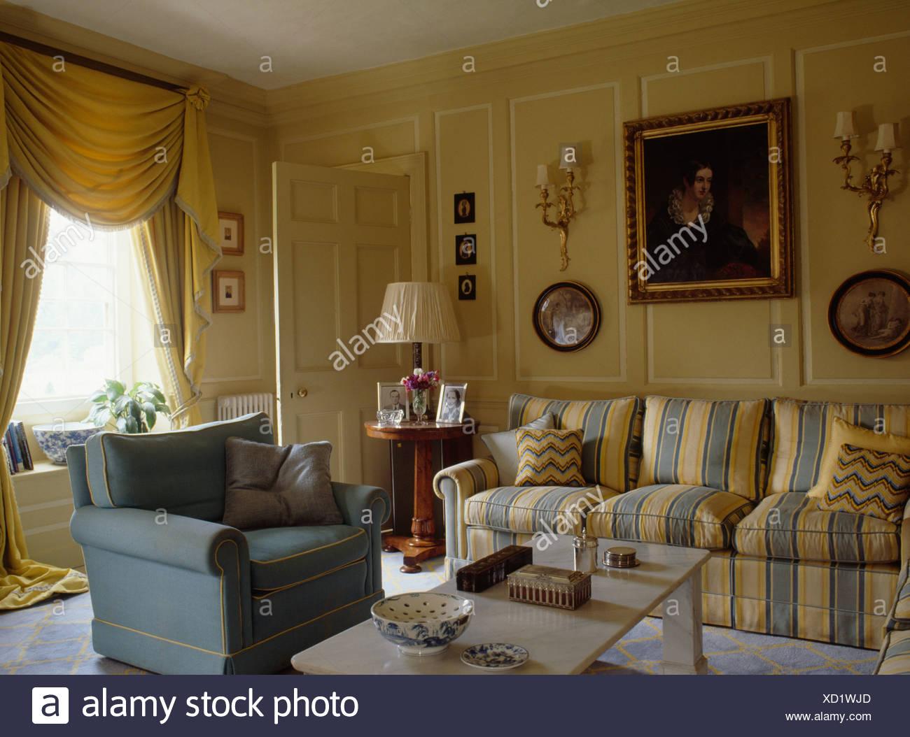 Gelb und blau gestreiften Sofa und blauen Sessel in Creme getäfelten ...