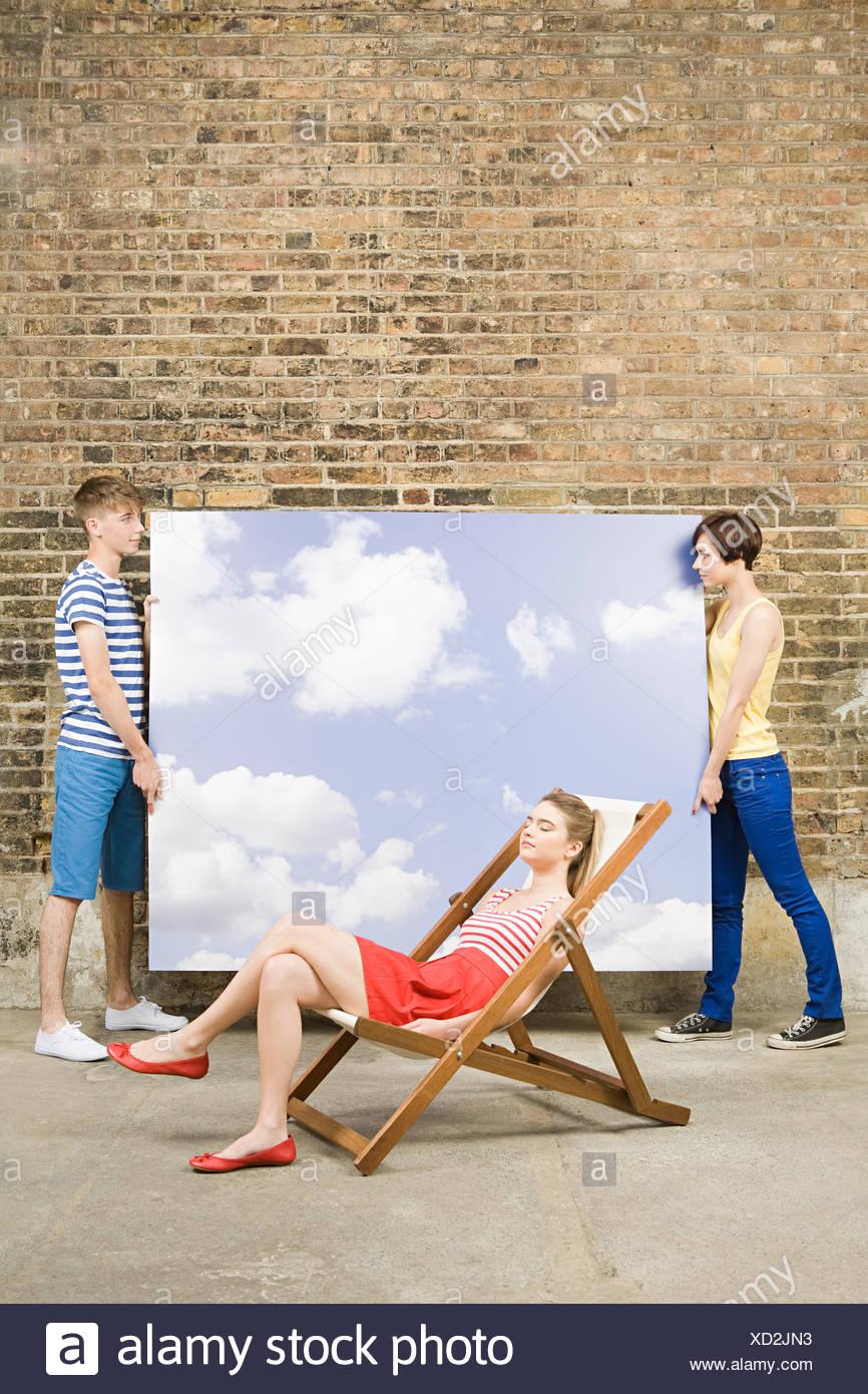 Junge Frau im Liegestuhl und andere mit Himmel Hintergrund Stockfoto