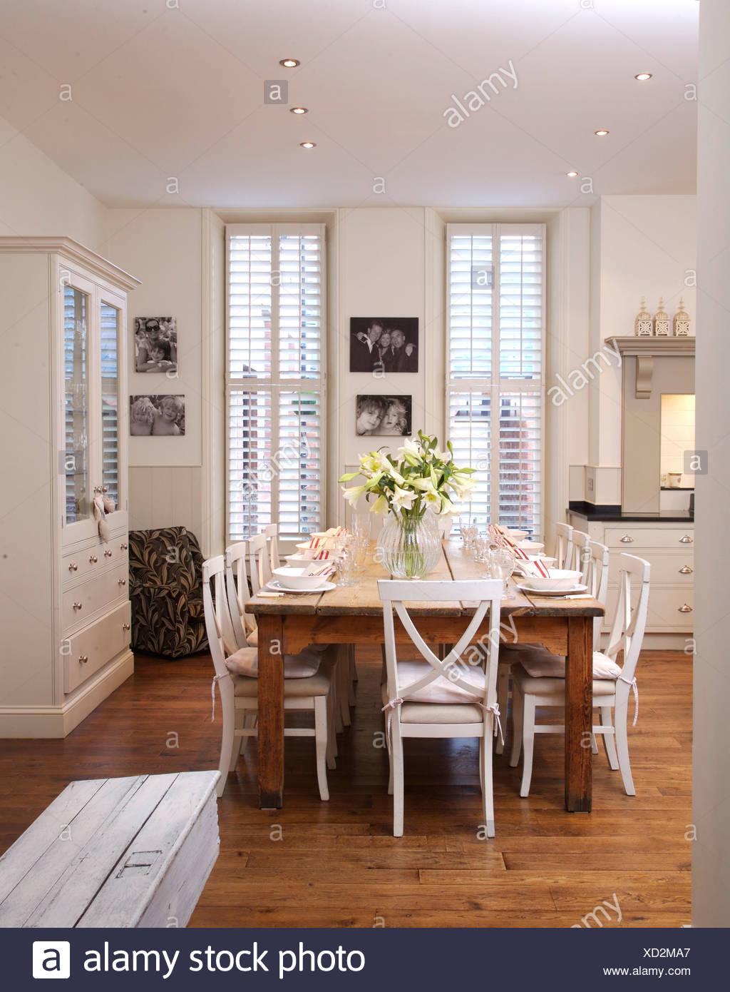 Weisse Stuhle Bei Einfachen Holztisch In Modernen Weissen Kuche Esszimmer Mit Parkettboden Und Weisse Plantage Fensterladen Stockfotografie Alamy