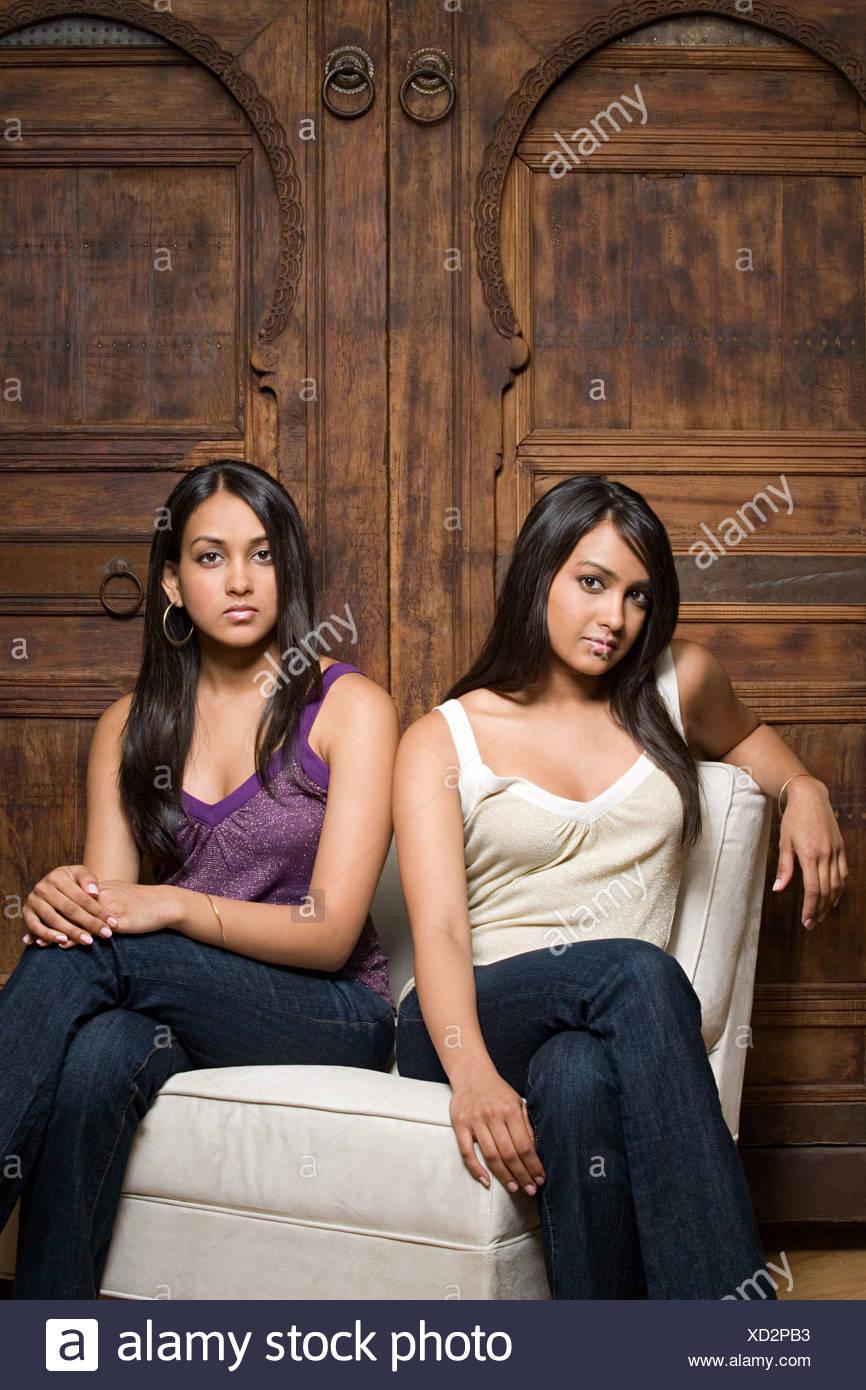 Indische Schwestern teilen einen Stuhl Stockbild