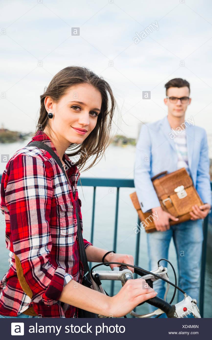 Deutschland, Mannheim, junge Frau auf der Brücke mit Mann im Hintergrund Stockbild