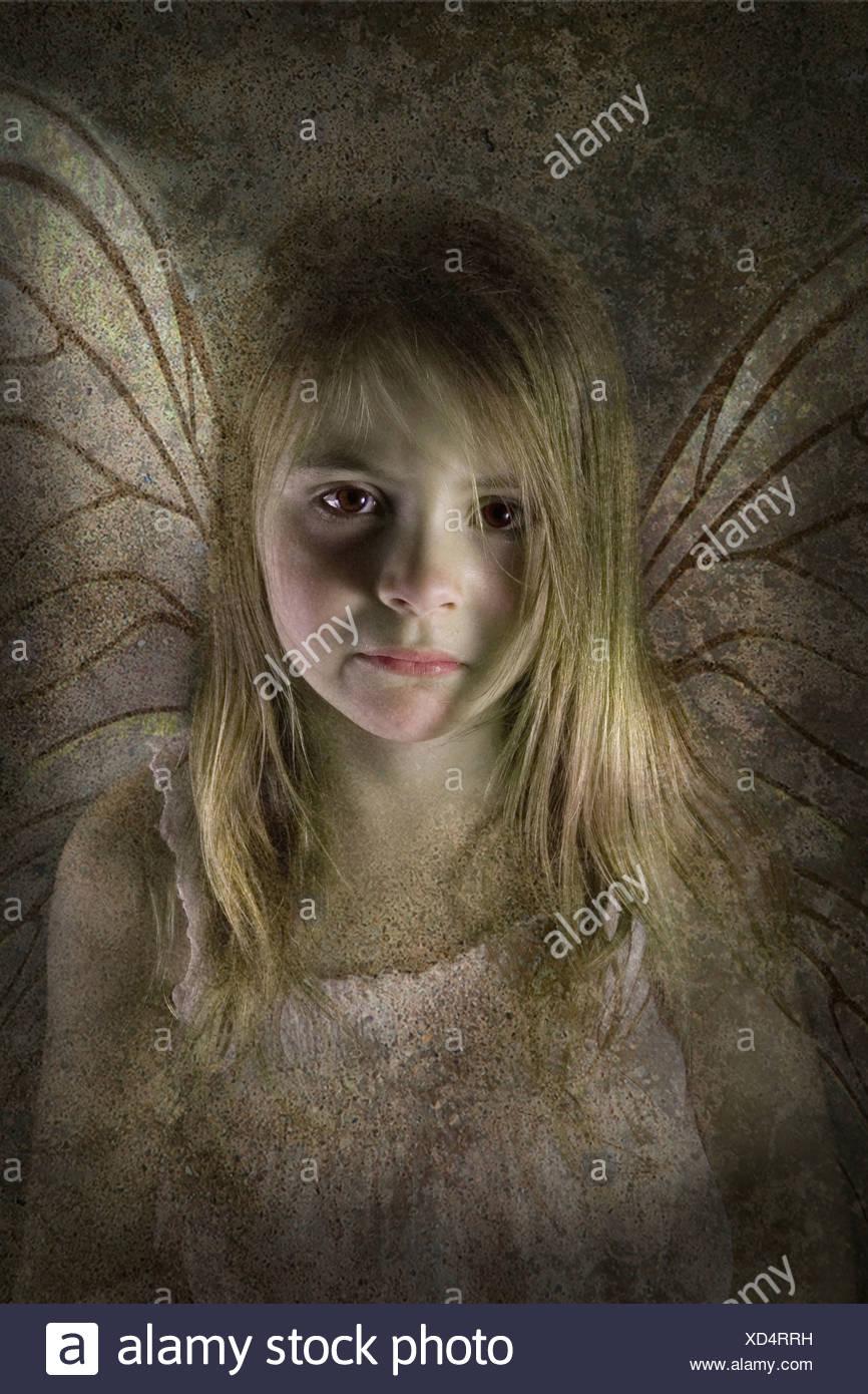 Junge Fee Kind mit Flügeln, die traurig und öde direkt in die Kamera schauen Stockbild