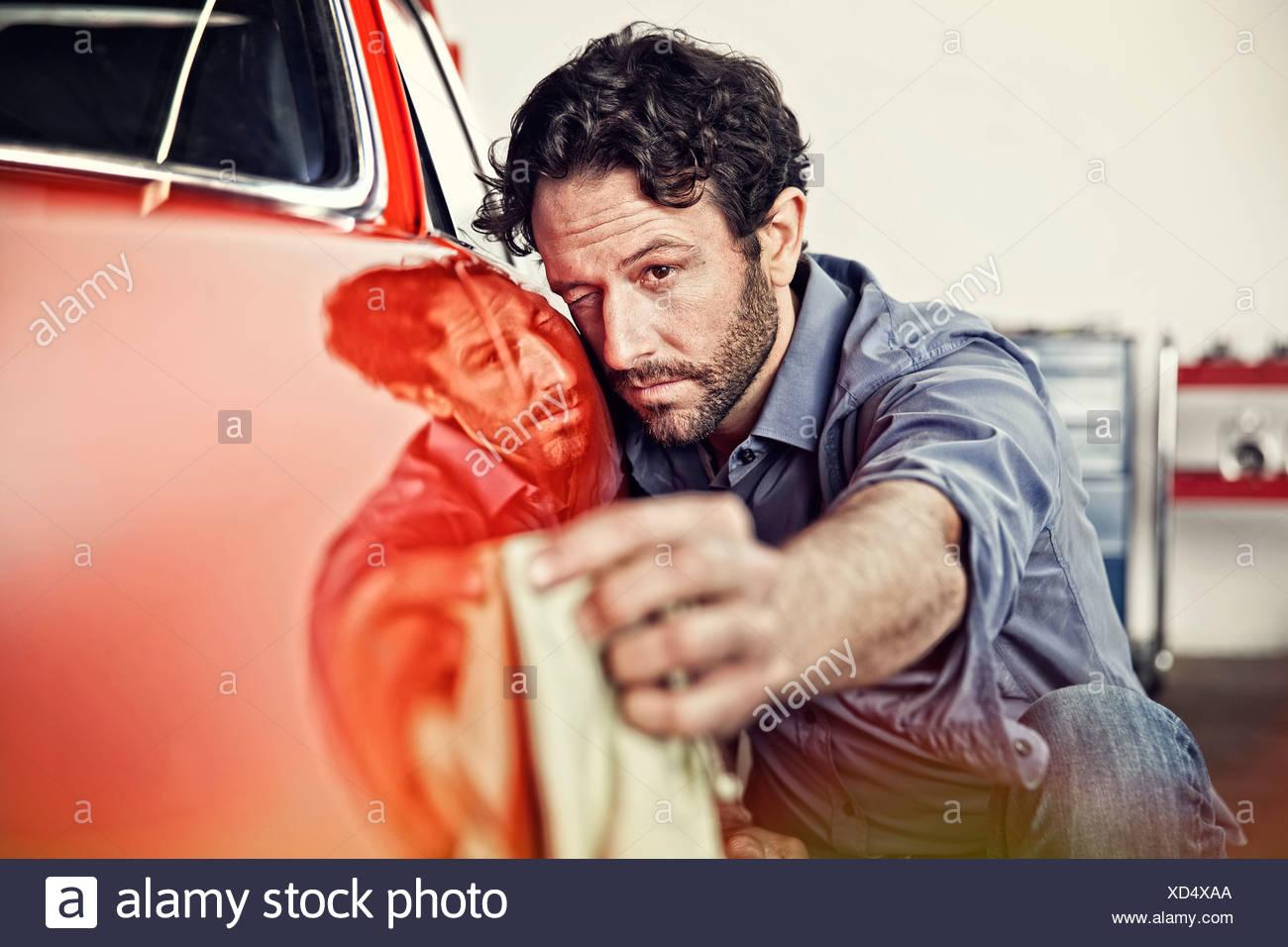Mann seinen Oldtimer Polieren Stockbild