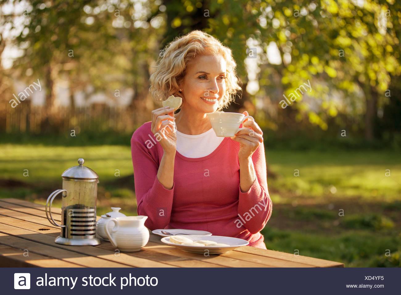 Eine reife Frau mit Kaffee und Gebäck in einem Garten Stockbild