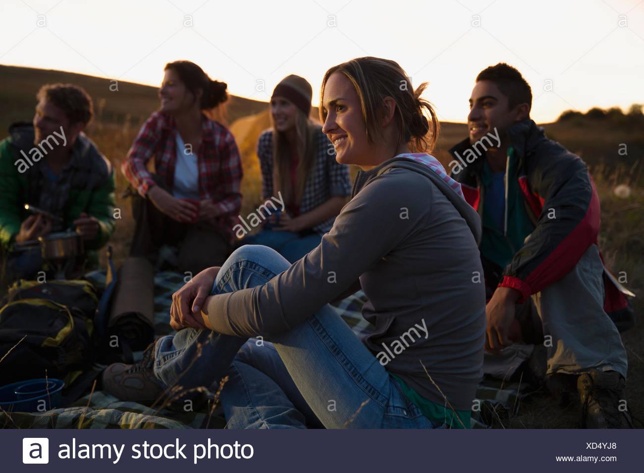 Freunde im Freien sitzen in der Abenddämmerung. Stockbild
