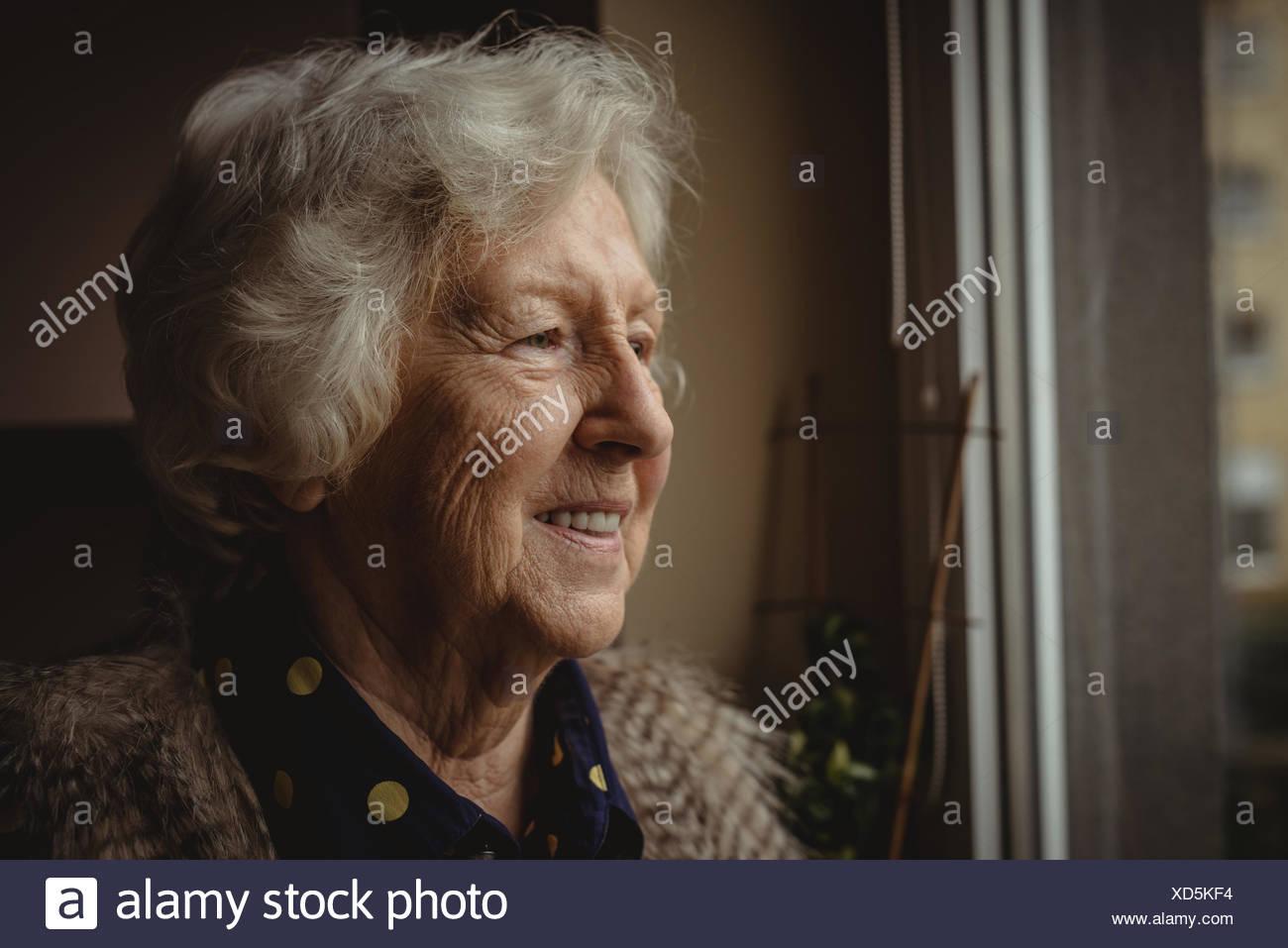 Lächelnde ältere Frau auf der Suche aus dem Fenster Stockbild