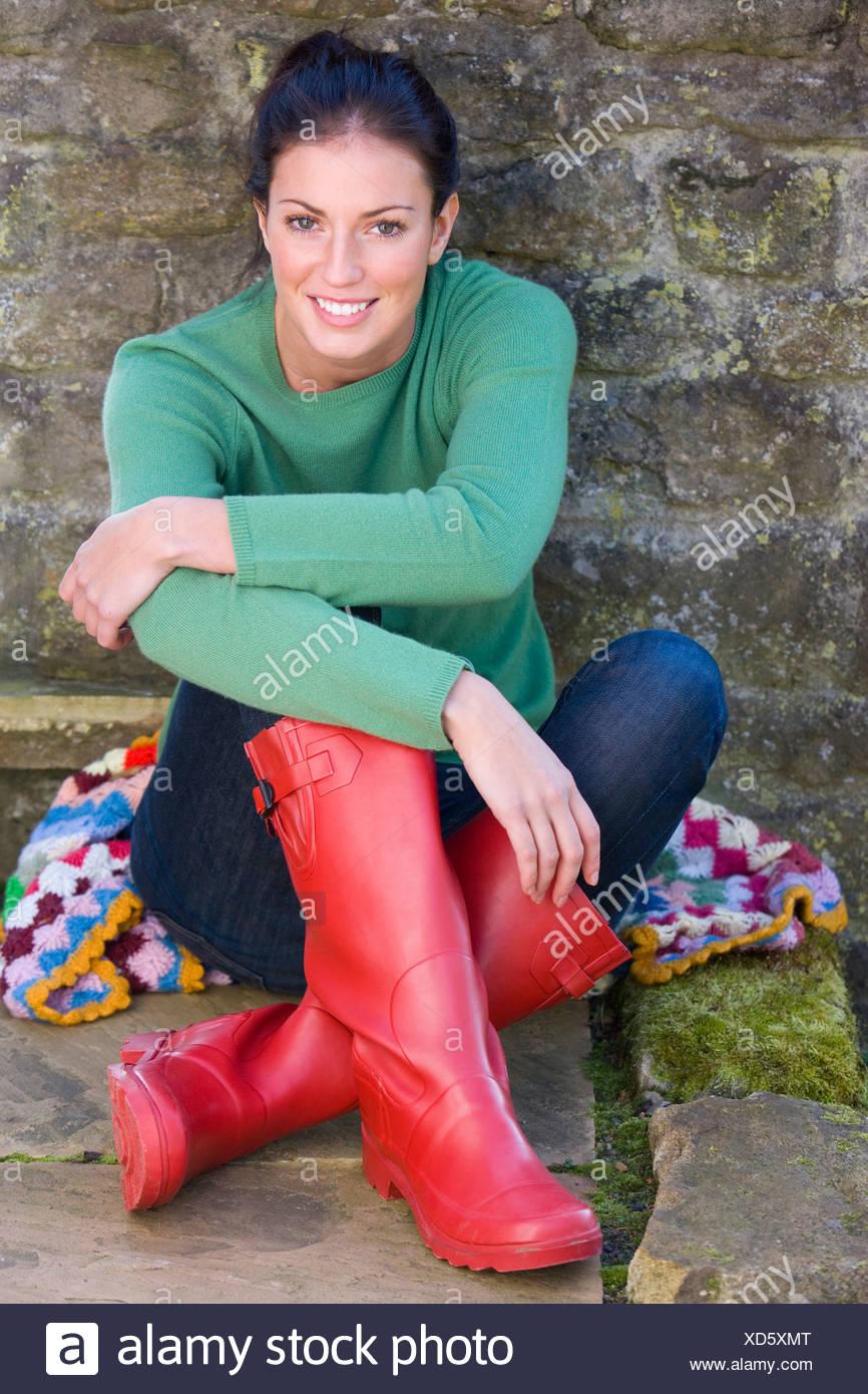 half off d105d 600b3 Lächelnde Frauen in Gummistiefel Wand gelehnt Stockfoto ...