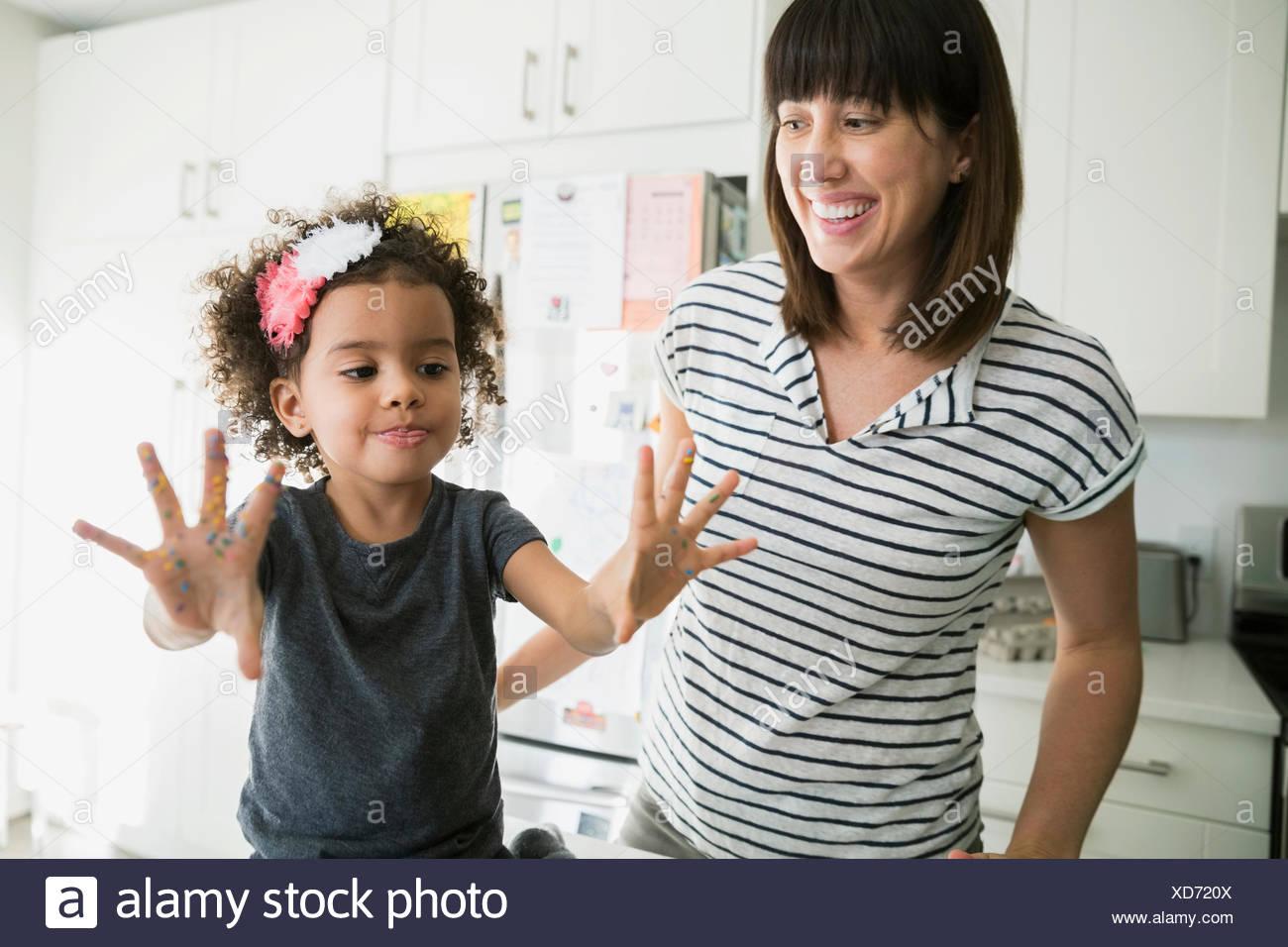 Mutter Tochter zeigen chaotisch Backen Hände ansehen Stockbild