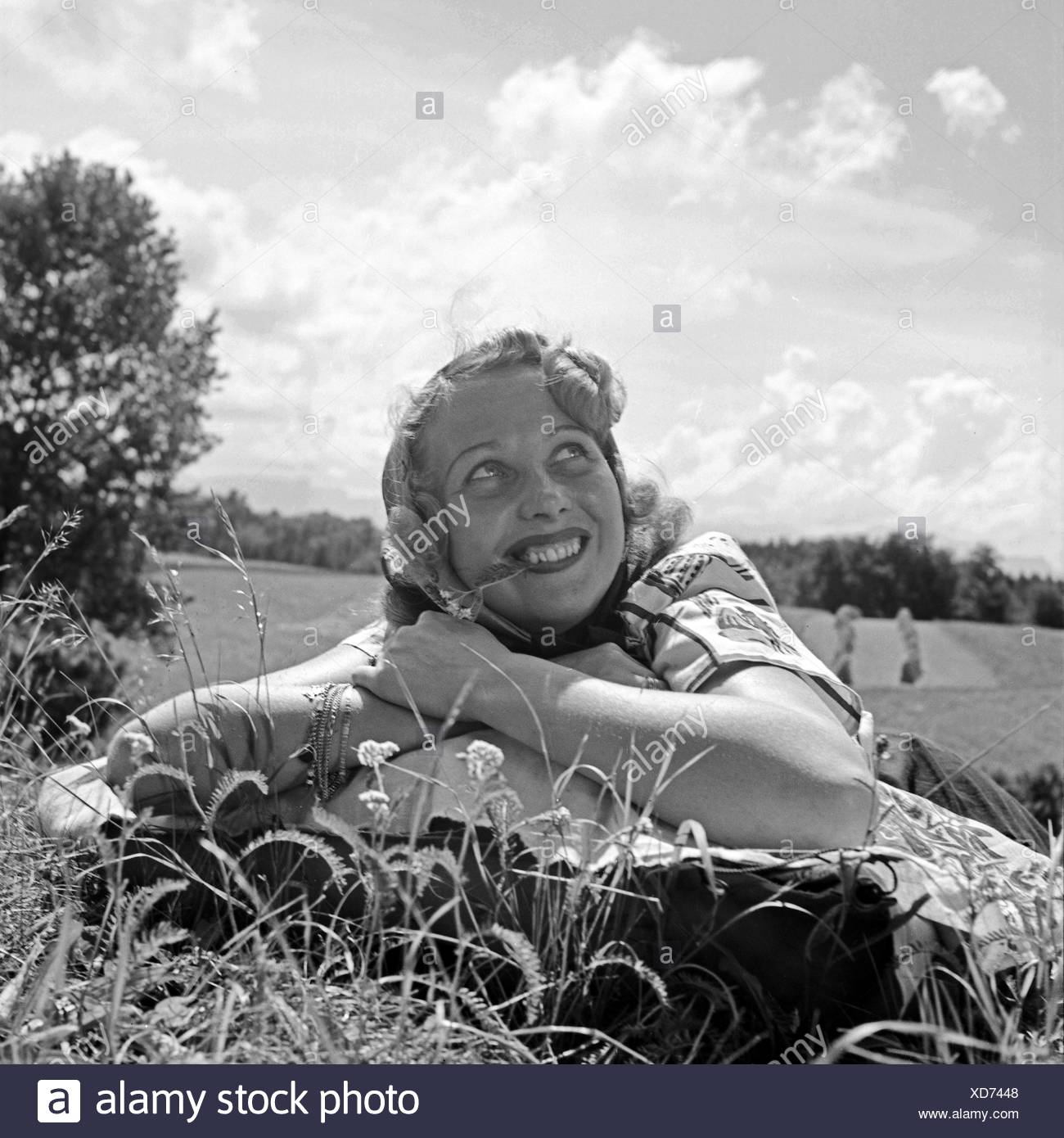 Eine Junge Frau so Lachen in Einer Wiese, 1930er Jahre Deutschland. Eine junge Frau auf der Wiese liegend lächelnd, Deutschland der 1930er Jahre. Stockbild