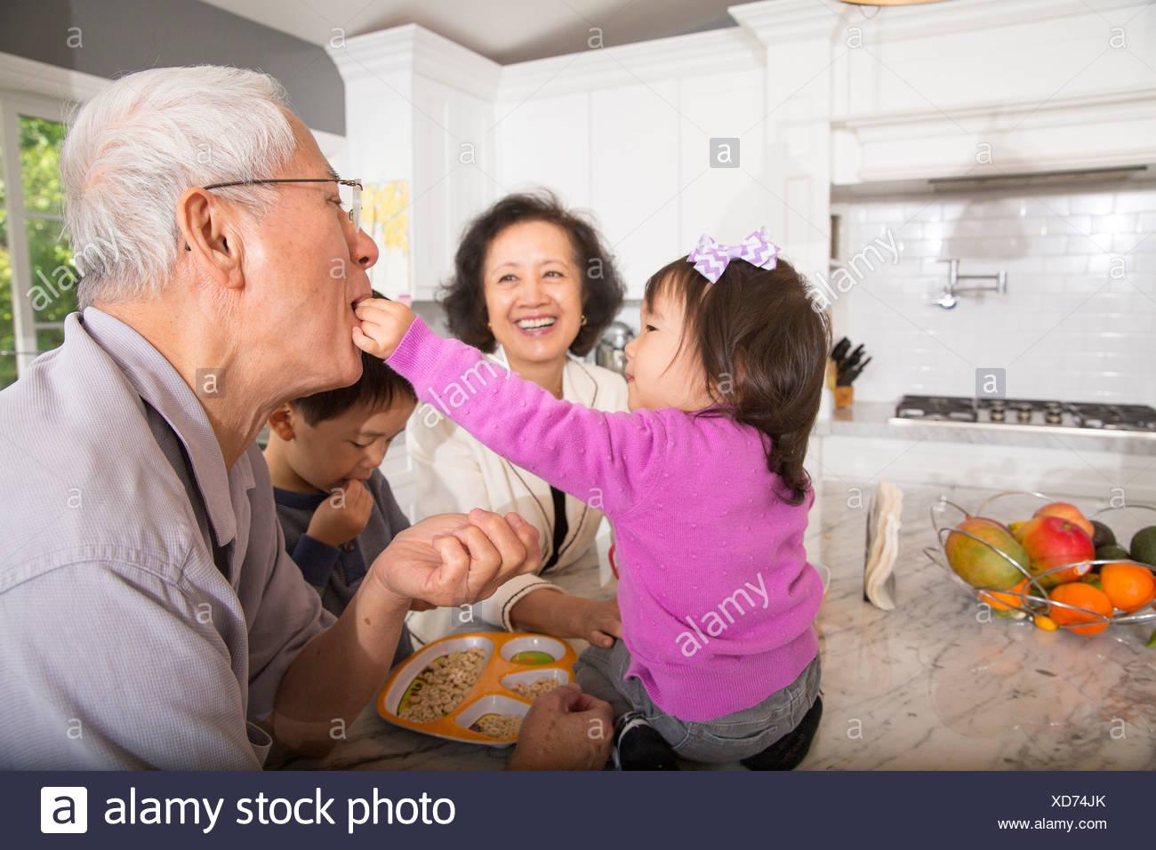 Weiblichen Kleinkind füttern Snack Großvater in Küche Stockbild