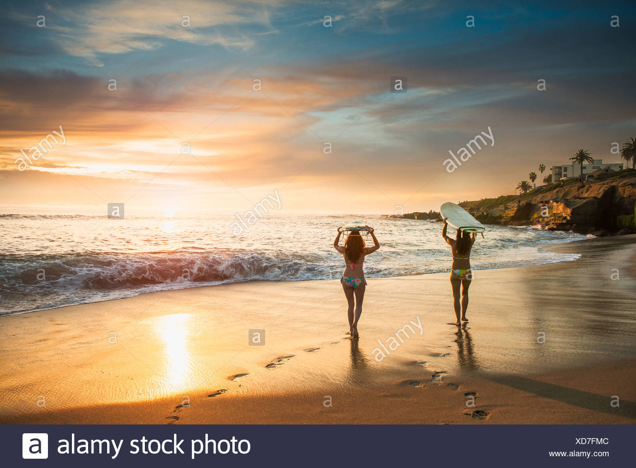 Surfer mit Surfbrett, Strand entlang spazieren Stockbild
