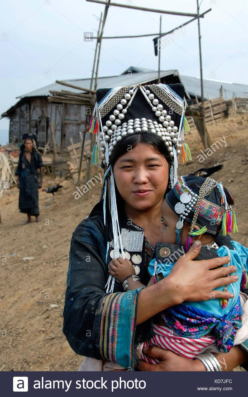 Mutter des Stammes Akha Meuo gekleidet in traditioneller Tracht, hält ihr Baby in ihren Armen, im Rücken die Großmutter, Ban Ch Stockbild