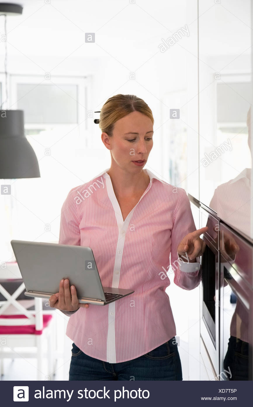 Frau mit Laptop in Küche Stockbild