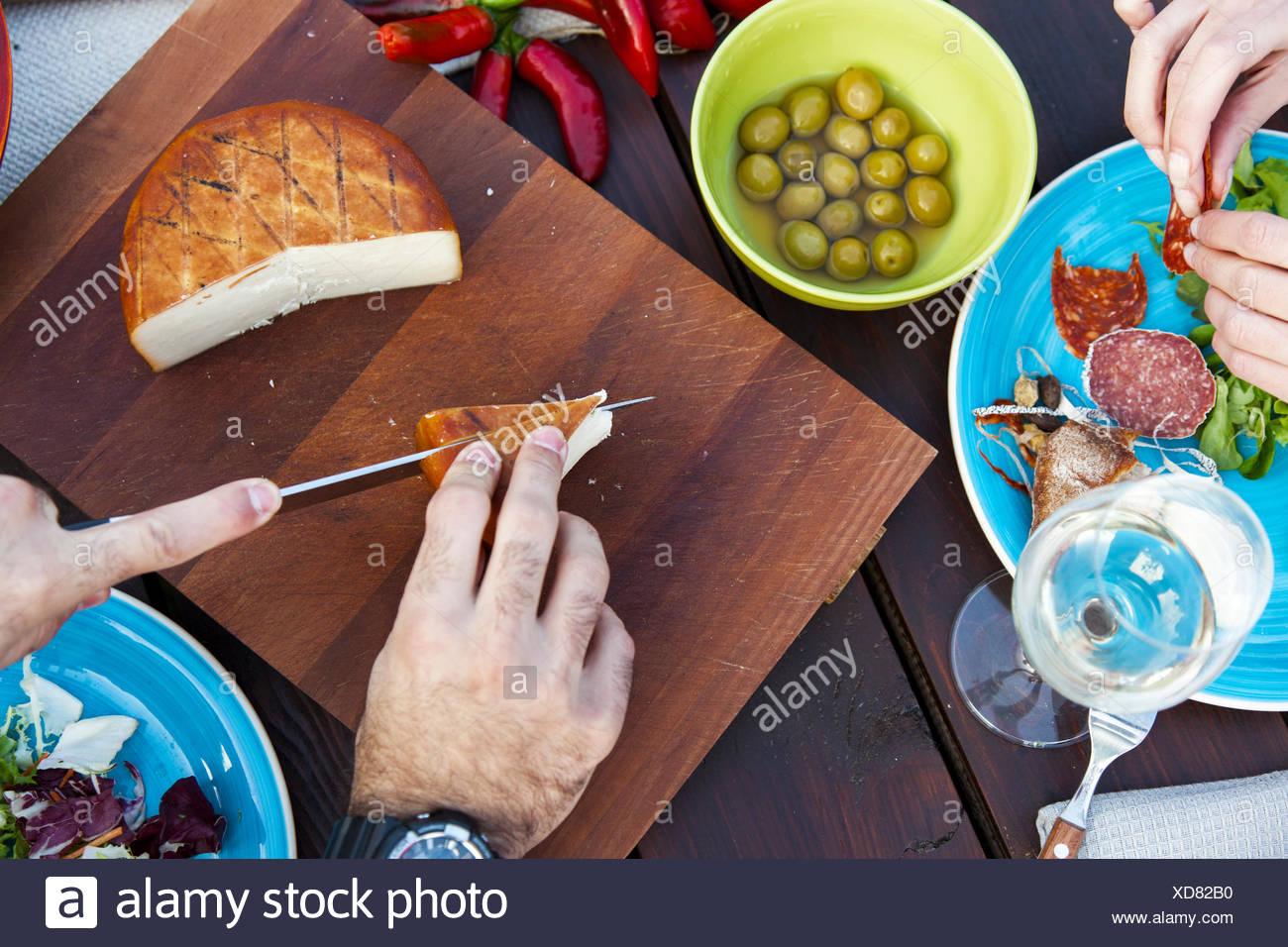 Mann schneiden Käse auf der Gartenparty Stockbild