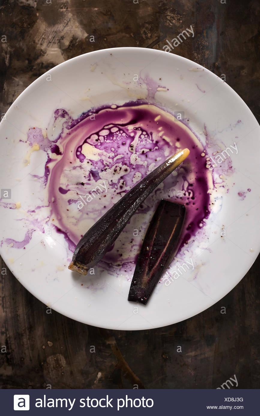 Violette Möhre auf einem weißen Teller mit lila Säfte und Öl eine unordentliche Mischung auf einer rustikalen Metalloberfläche zu schaffen. Stockbild