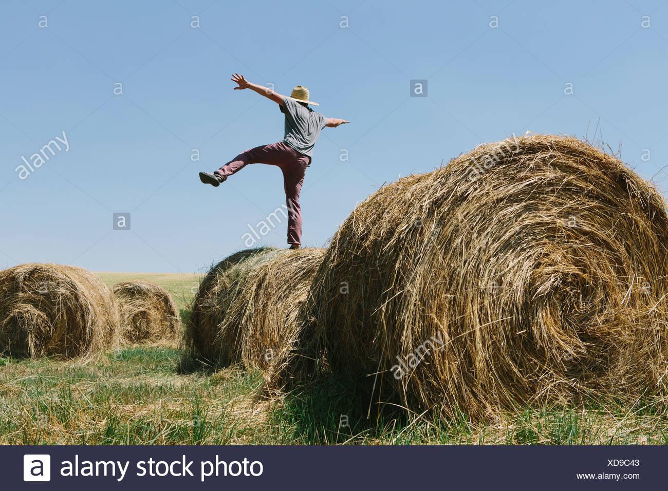 Rückansicht eines Mannes balancieren auf einem Bein auf einem Heuballen. Stockfoto