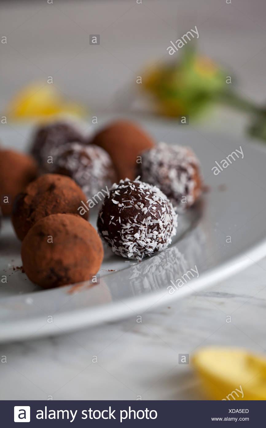 Vegane Schokolade Mandel Datum Kugeln auf einem weißen Teller Stockbild