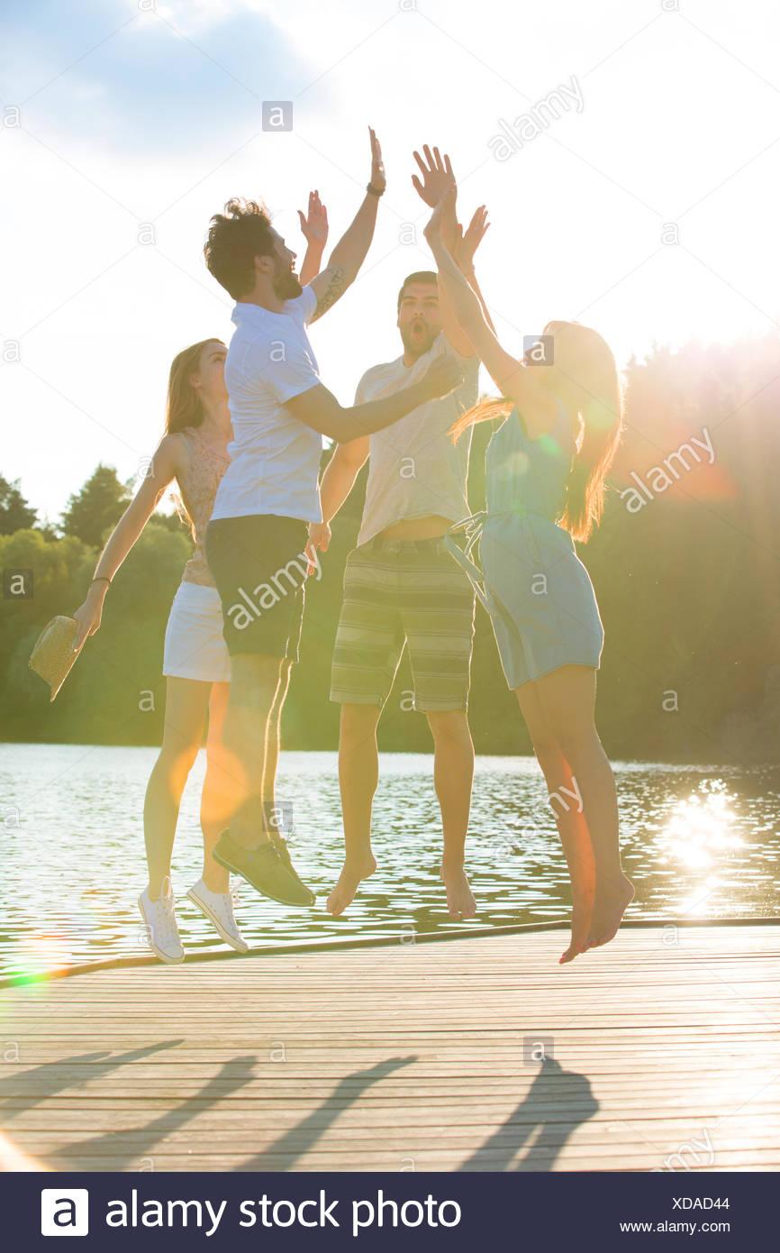 Vier Freunde hohe Fiving an einem See bei Gegenlicht Stockbild